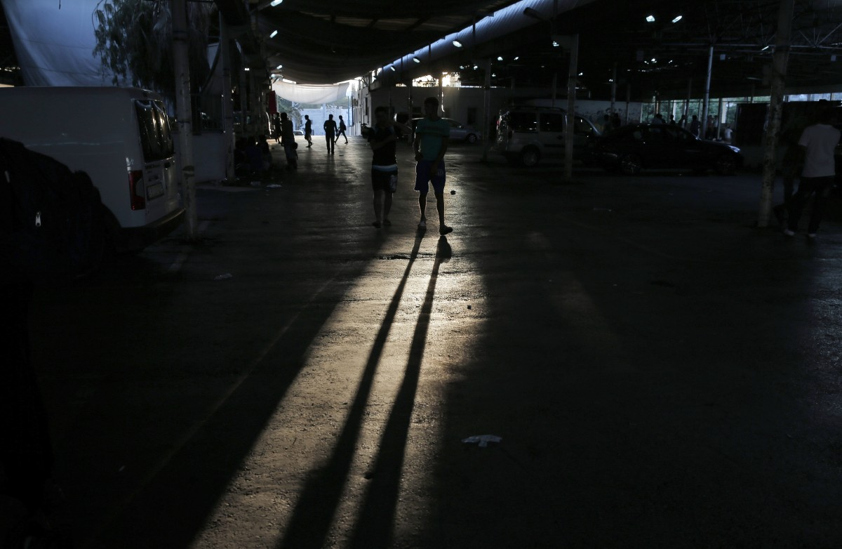 Migrants walk through the bus station market area where they sought shelter, in the coastal town of Bodrum, Turkey, until they try to cross with boats into Greece, Sunday, Aug. 16, 2015. The city of Bodrum, a magnet for wealthy tourists, is these days drawing plenty of other visitorsó migrants fleeing conflicts in the Middle East and Africa and seeking a better life in Europe. At its closest point, the Greek island of Kos is only 4 kilometers (2.5 miles) from Turkey and migrants, mostly from Syria, but also from Afghanistan, Iran and African nations often try to cross in groups upward of eight people in small inflatable plastic boats meant for a maximum of four, powered by tiny electric outboard motors and plastic paddles. (AP Photo/Lefteris Pitarakis)