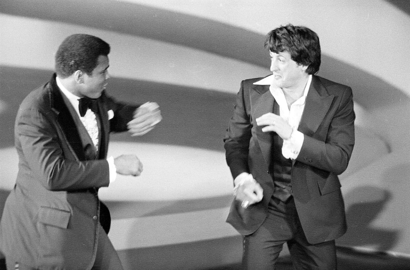 "FILE – In this March 28, 1977, file photo, heavyweight boxing champion Muhammad Ali, left, makes a surprise appearance on the Academy Awards show, playfully sparring with actor and screenwriter Sylvester Stallone, right, in Los Angeles. Four decades after the Nov. 21, 1976, premiere of ""Rocky,"" the movie's reach is international, and the title character's underdog tale of determination, grit and sleepy-eyed charm still resonates with fans. (AP Photo, File)"