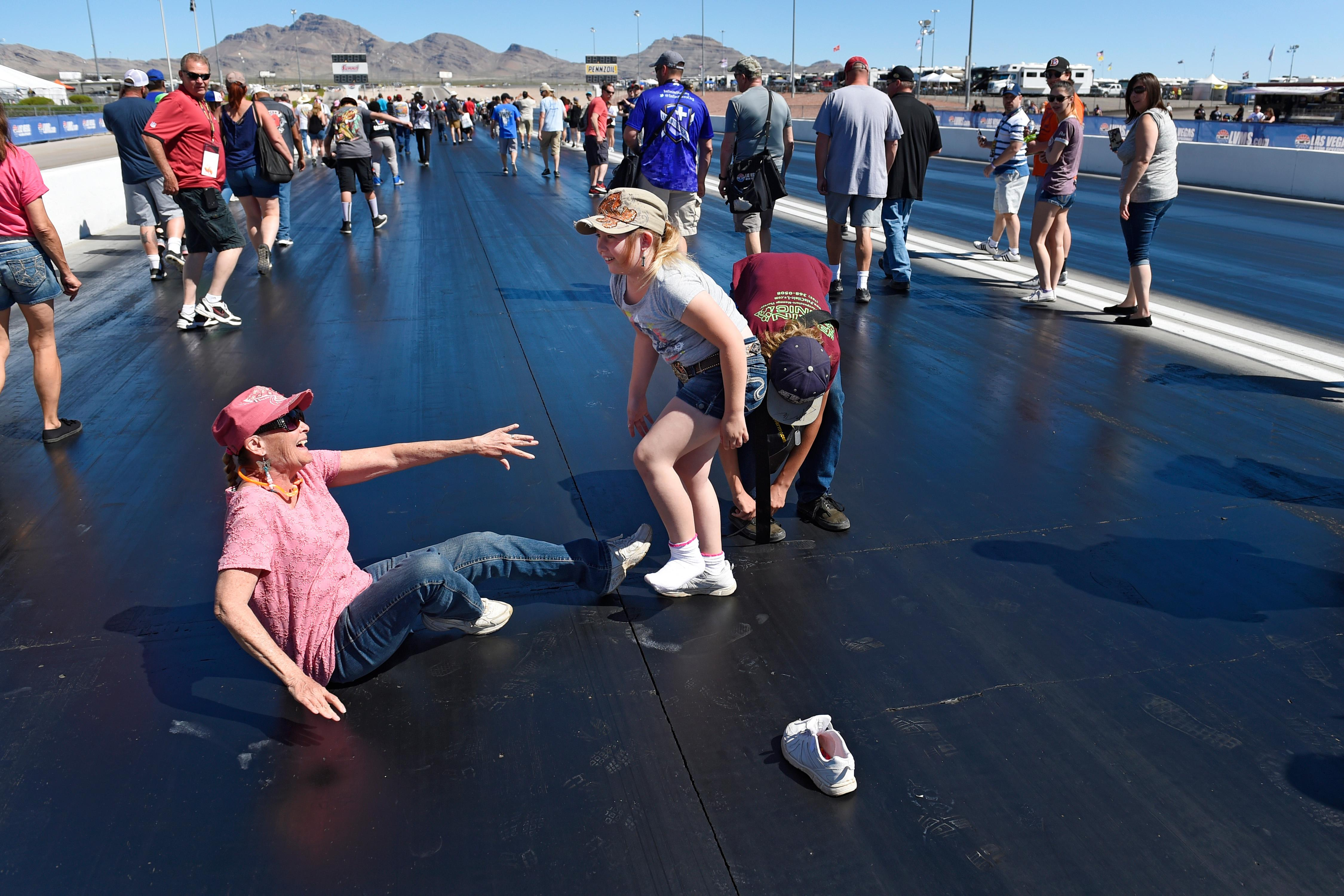 Goldie Dollarhide reaches for help from Macy Dollarhide, who has lost her shoe, during the track walk before the NHRA DENSO Spark Plug Nationals at The Strip at the Las Vegas Motor Speedway Sunday, April 2, 2017. (Sam Morris/Las Vegas News Bureau)