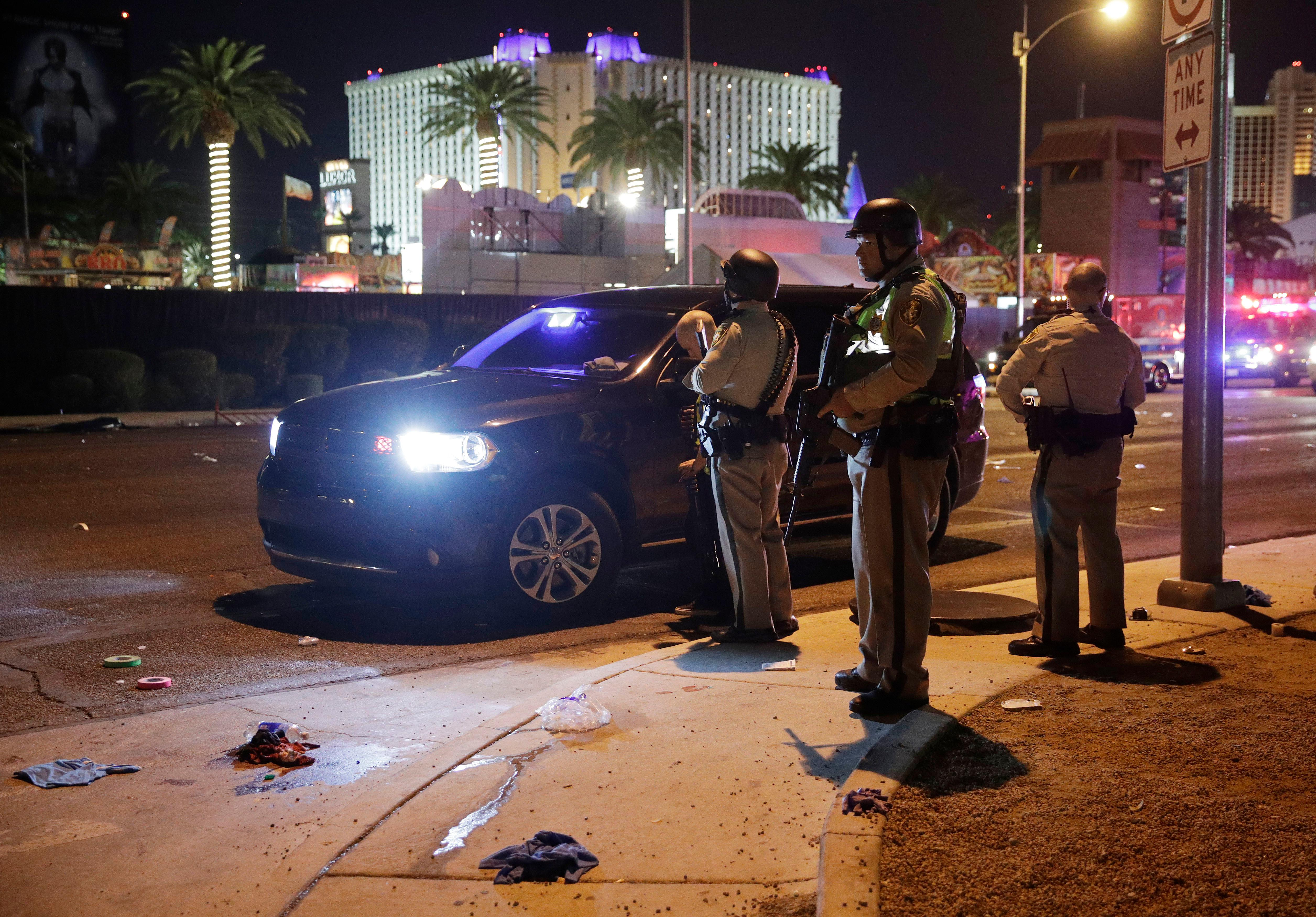 Las Vegas Police stand at the scene of a shooting along the Las Vegas Strip, Monday, Oct. 2, 2017, in Las Vegas. Multiple victims were being transported to hospitals after a shooting late Sunday at a music festival on the Las Vegas Strip. (AP Photo/John Locher)