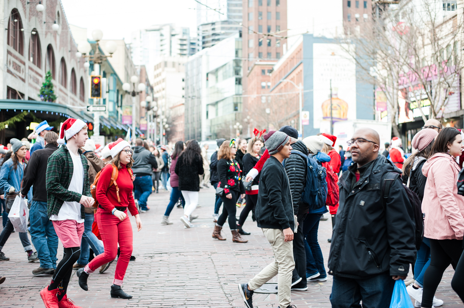 "Thousands of Santas flooded the streets of Seattle for the annual Seattle SantaCon. Festive fans packed bars downtown in Santa, Elf and Reindeer attire. The focus is on spontaneity and creativity, while having a good time and spreading cheer and goodwill. And their #1 rule? ""My name is Santa. Your name is Santa. We are Santa. Who's in charge here? Santa!"" (Image: Elizabeth Crook / Seattle Refined){ }"
