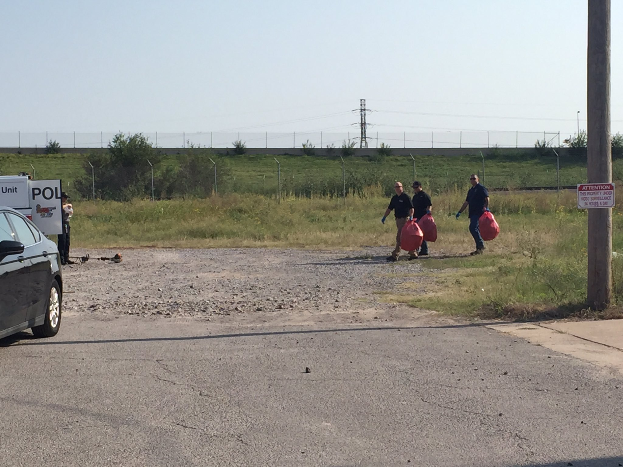 Officers are walking away from the scene carry red (what looks like bio-hazard) bags.  (Jordann Lucero / KOKH)