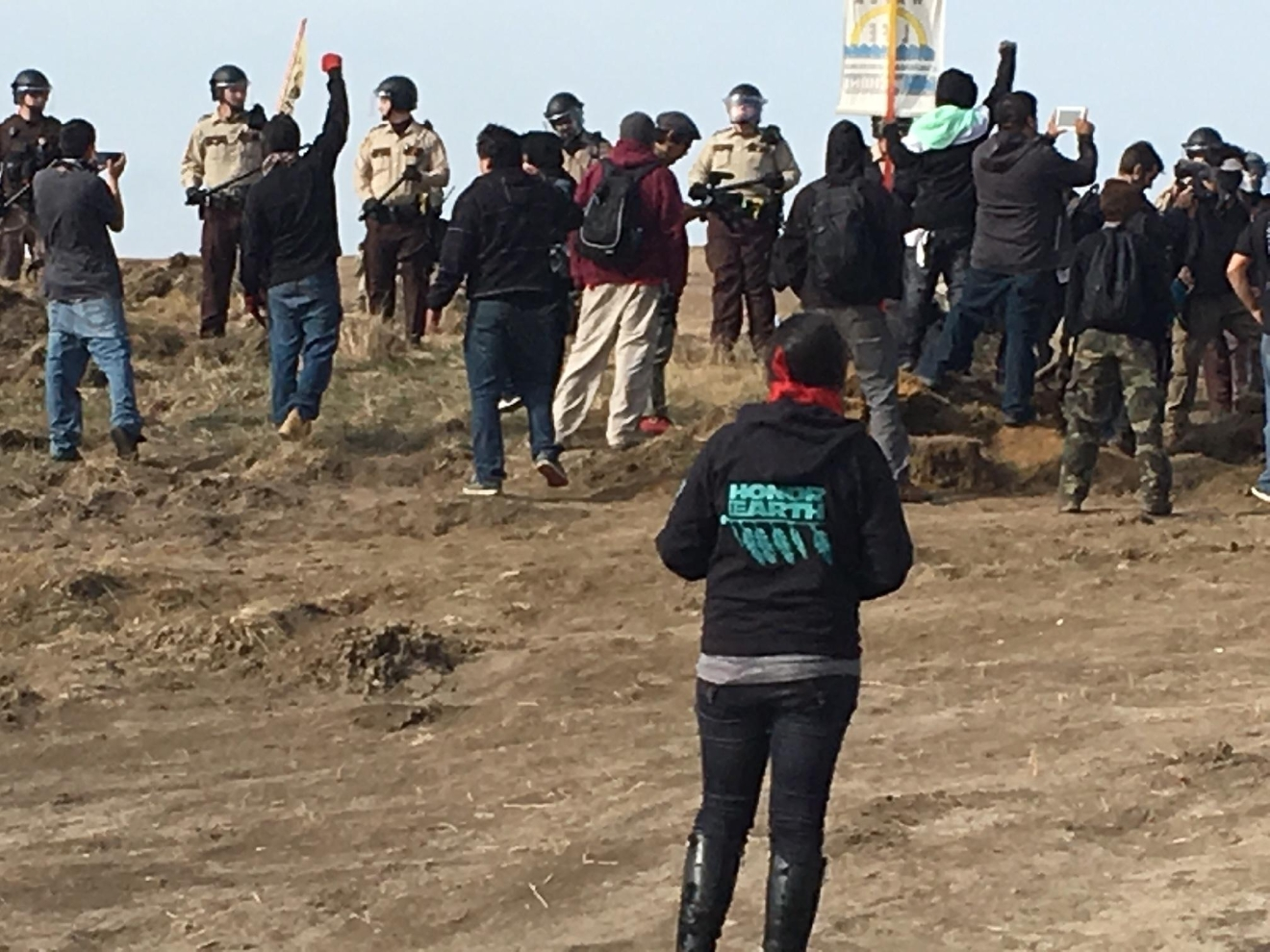 Demonstrators cheer as armed soldiers and law enforcement officers move in to force Dakota Access pipeline protesters off private land in North Dakota on Thursday, Oct. 27, 2016, where they had camped to block construction. The pipeline is to carry oil from western North Dakota through South Dakota and Iowa to an existing pipeline in Patoka, Ill. (Mike McCleary/The Bismarck Tribune via AP)