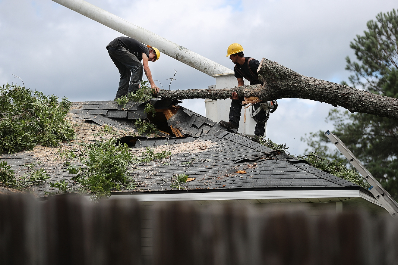 A tree service company removes a fallen tree from the roof of a damaged home Friday, Sept. 2, 2016, in Valdosta. Ga., in the aftermath of Tropical Storm Hermine. (Curtis Compton/Atlanta Journal-Constitution via AP)