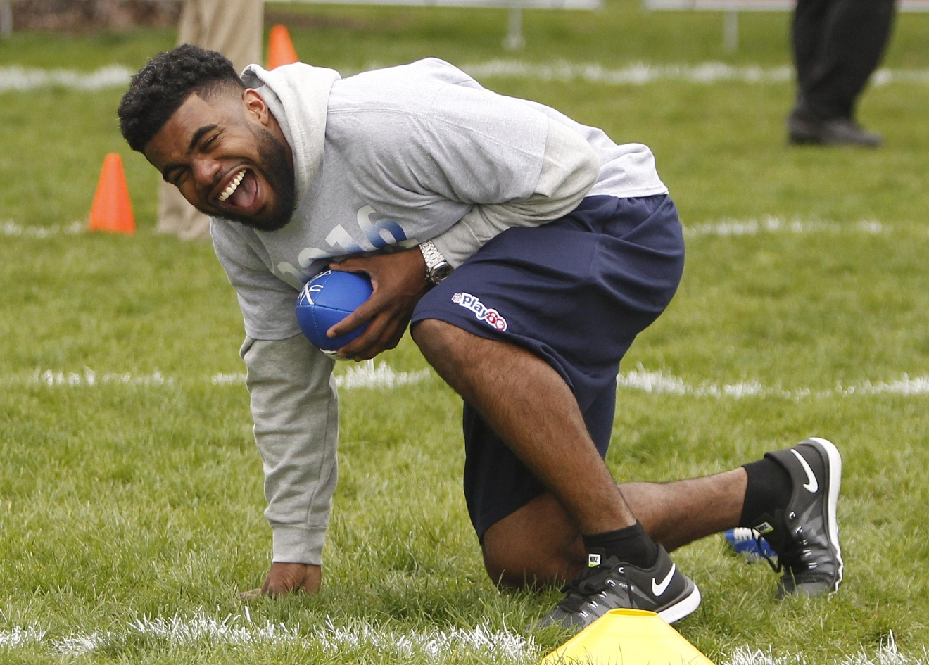 Ohio State's Ezekiel Elliott kneels as he laughs with other athletes during an NFL Play 60 event at Grant Park, Wednesday, April 27, 2016, in Chicago before Thursday's first round of the NFL football draft. (AP Photo/Kiichiro Sato)