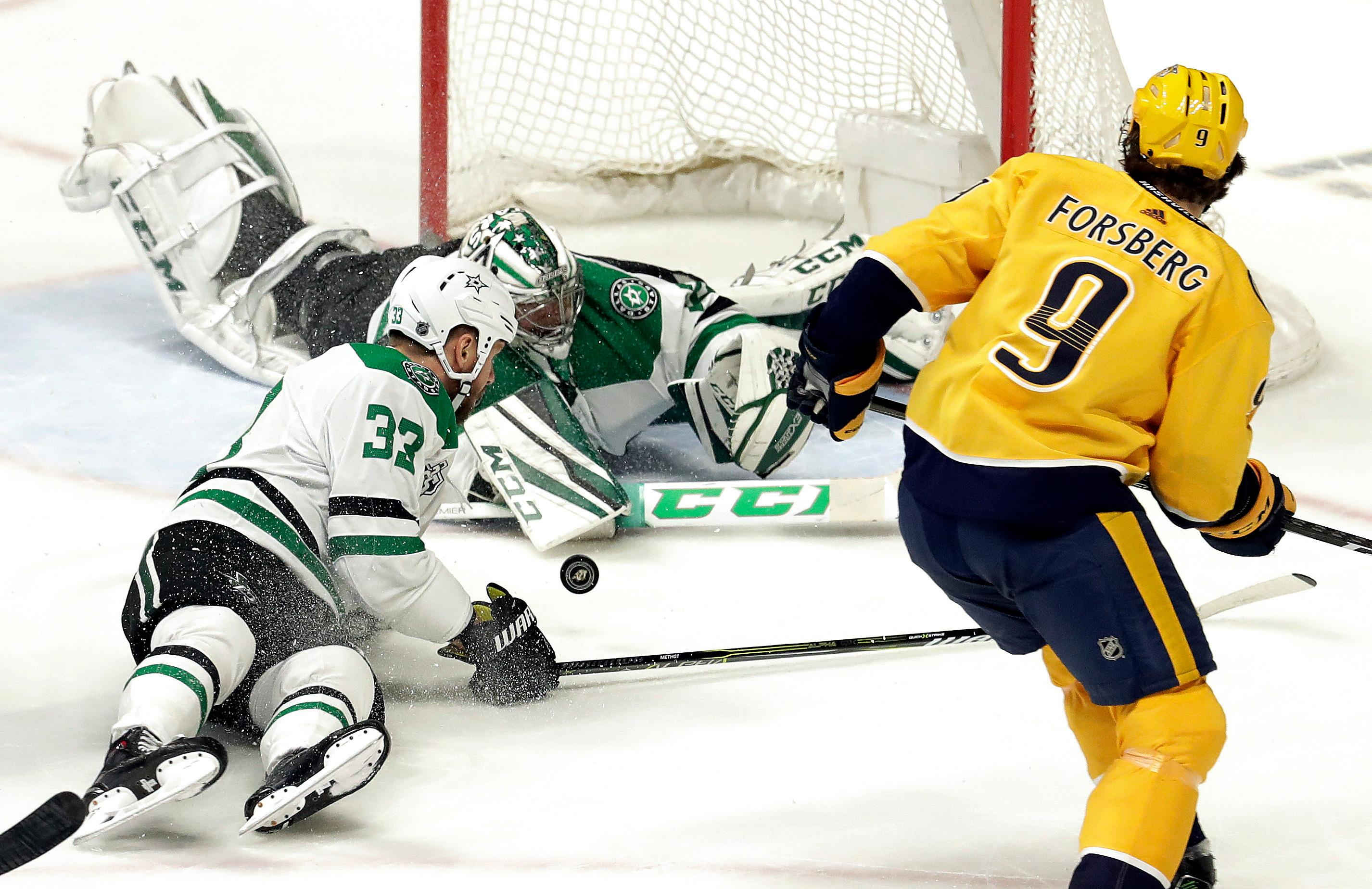 Dallas Stars goalie Kari Lehtonen, of Finland, and defenseman Marc Methot (33) surround the puck as Nashville Predators left wing Filip Forsberg (9), of Sweden, closes in during the third period of an NHL hockey game Tuesday, March 6, 2018, in Nashville, Tenn. The Predators won 2-0. (AP Photo/Mark Humphrey)