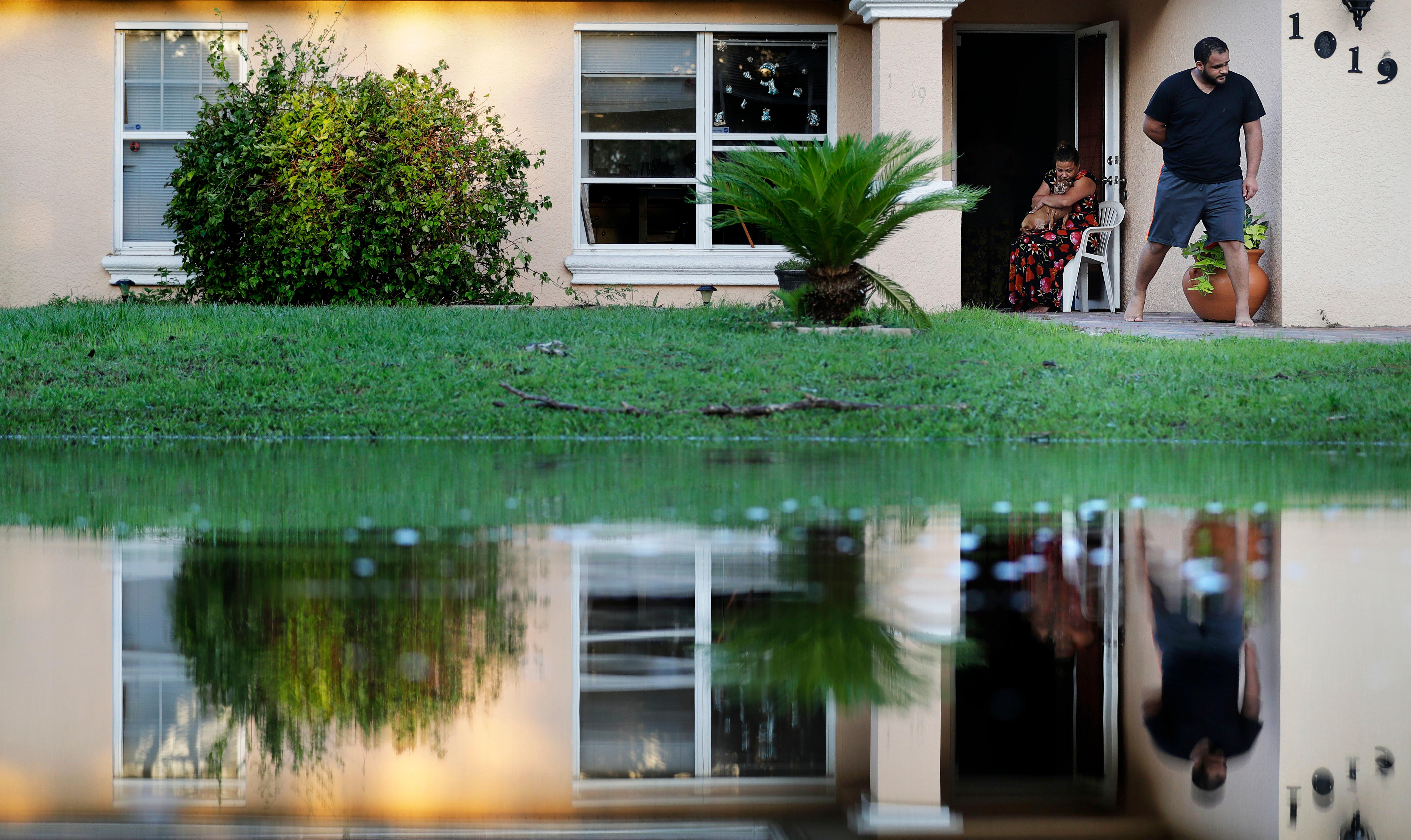 "Sandra Pagan, left, escapes the heat inside her home with her dog Goldo and nephew Misael Fernandez after Hurricane Irma flooded their neighborhood leaving them without power and impassable with their cars in Fort Myers, Fla., Tuesday, Sept. 12, 2017. ""It's unbearable,"" said Pagan who rode out the storm in the home with her family. ""We can't sleep at all. It's so hot."" (AP Photo/David Goldman)"