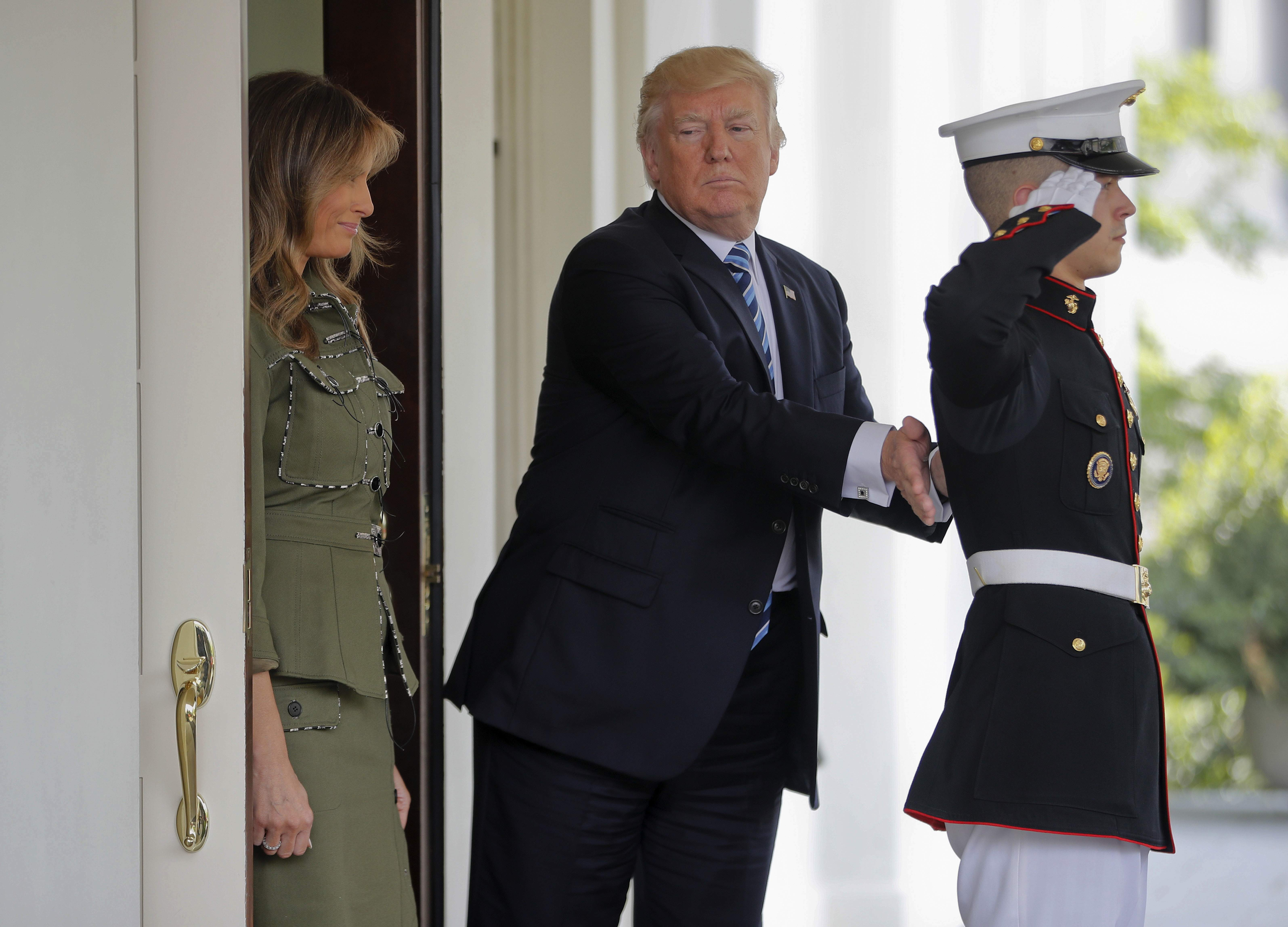 DAY 98 - In this April 27, 2017 photo, President Donald Trump pats a U.S. Marine on the back after he and first lady Melania Trump walked Argentine President Mauricio Macri and his wife Juliana Awada to their vehicle outside the West Wing of the White House in Washington. (AP Photo/Pablo Martinez Monsivais)