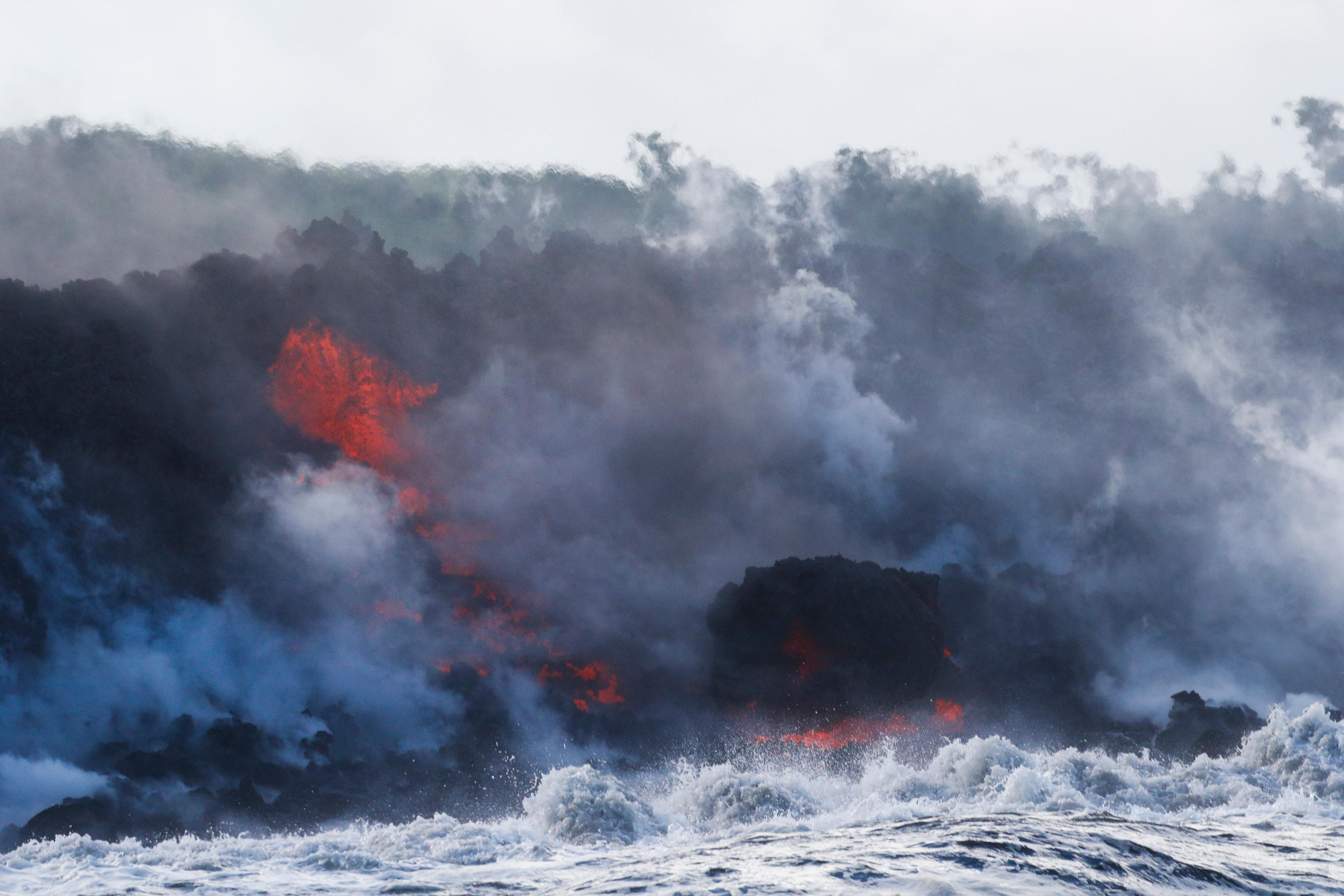 Lava flows into the ocean near Pahoa, Hawaii, Sunday, May 20, 2018. Kilauea volcano that is oozing, spewing and exploding on Hawaii's Big Island has gotten more hazardous in recent days, with rivers of molten rock pouring into the ocean Sunday and flying lava causing the first major injury. (AP Photo/Jae C. Hong)