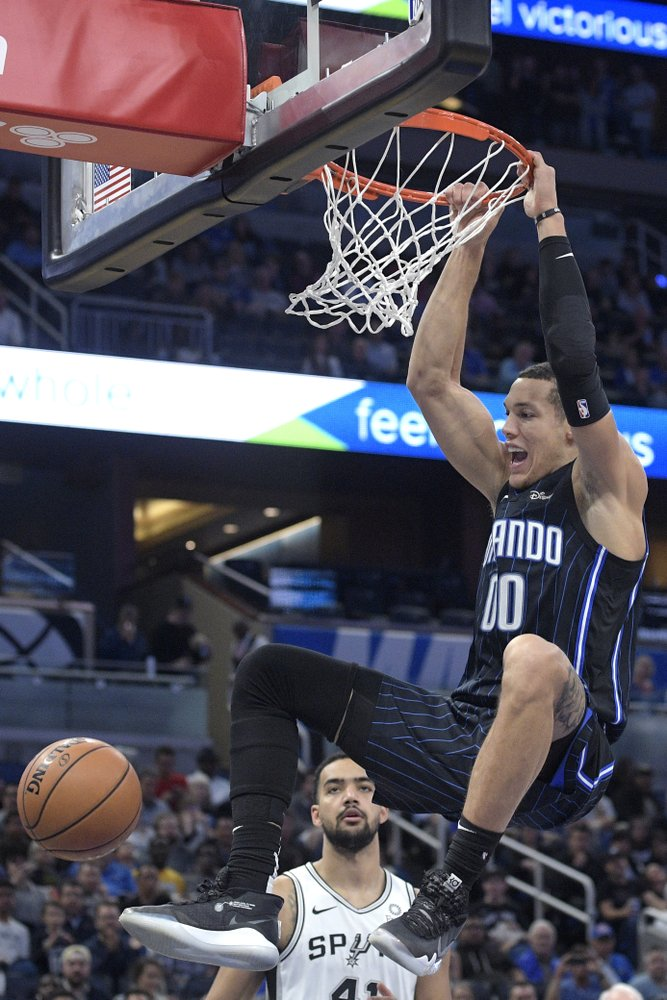 Orlando Magic forward Aaron Gordon (00) dunks in front of San Antonio Spurs center Trey Lyles during the first half of an NBA basketball game Friday, Nov. 15, 2019, in Orlando, Fla. (AP Photo/Phelan M. Ebenhack)