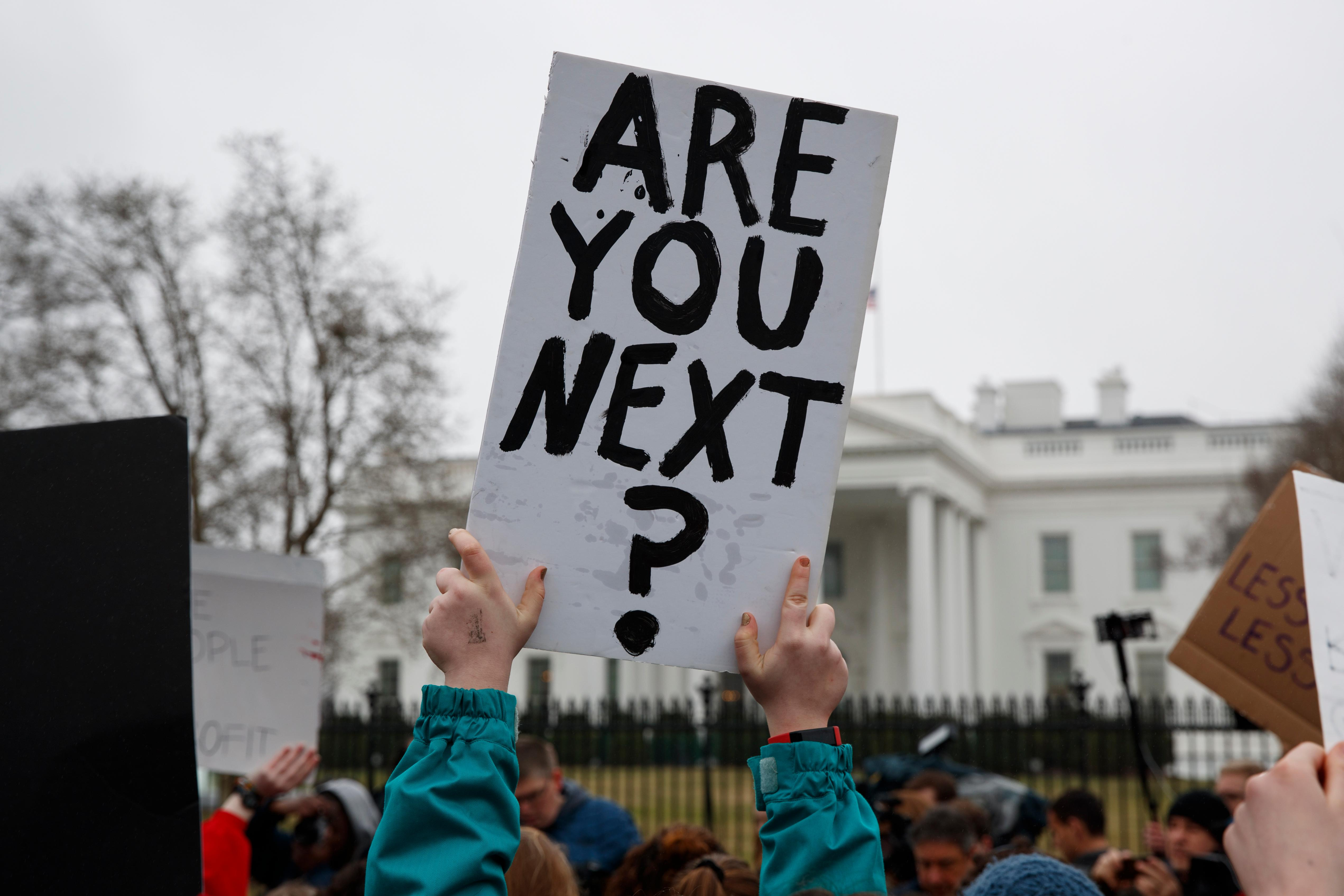 Demonstrators hold signs during a protest in favor of gun control reform in front of the White House, Monday, Feb. 19, 2018, in Washington. (AP Photo/Evan Vucci)
