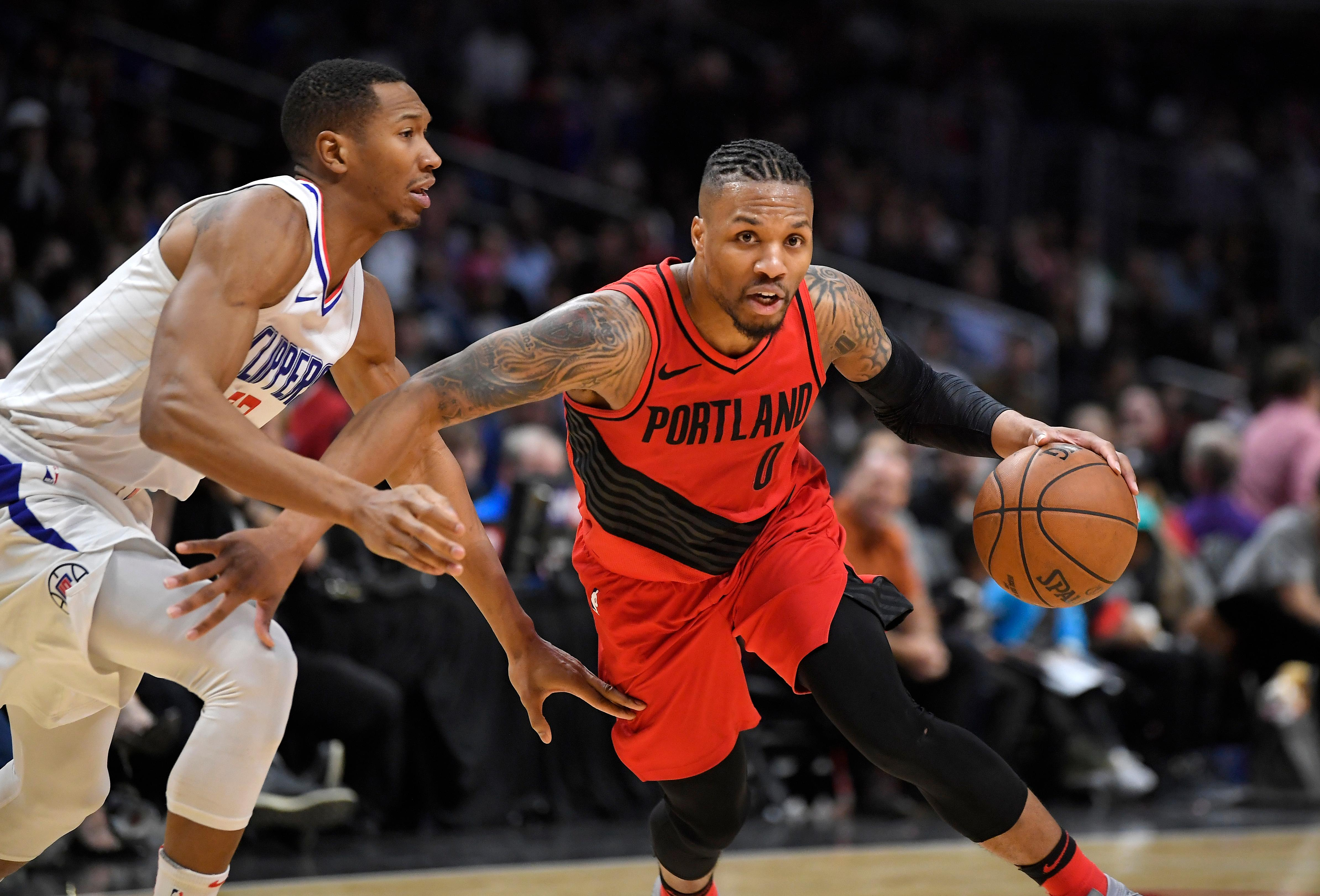 Portland Trail Blazers guard Damian Lillard, right, dribbles past Los Angeles Clippers forward Wesley Johnson during the second half of an NBA basketball game Tuesday, Jan. 30, 2018, in Los Angeles. The Trail Blazers won 104-96. (AP Photo/Mark J. Terrill)