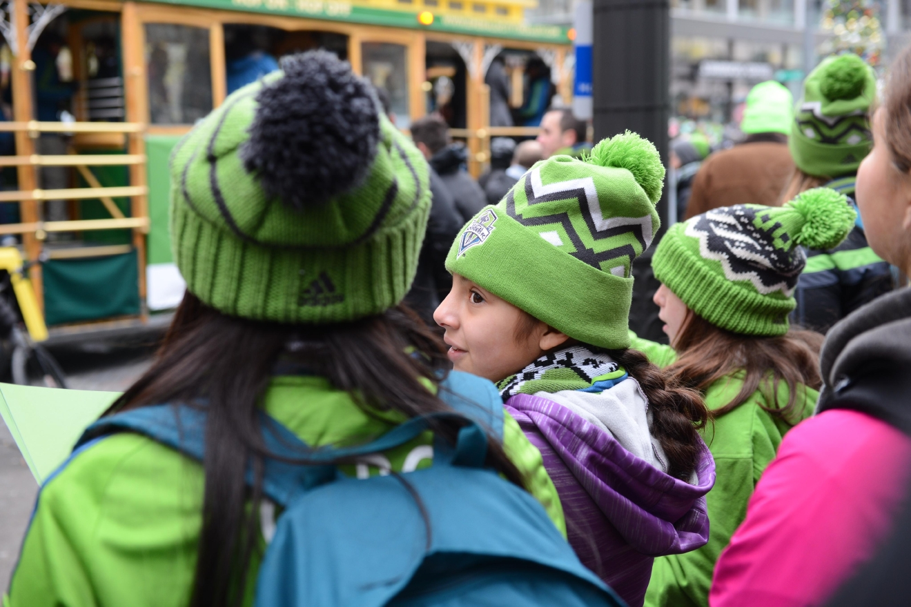 Downtown Seattle was swarmed with fans as the reigning MLS champions, the Seattle Sounders, paraded along 4th Avenue from Pine Street to Seattle Center, Thousands lined up along the route waving green and blue to catch a glimpse of the players and coaches. The Sounders defeated Toronto FC on Saturday, December 10, 2017 - winning the first MLS Cup victory in franchise history. (Image: Chona Kasinger / Seattle Refined)