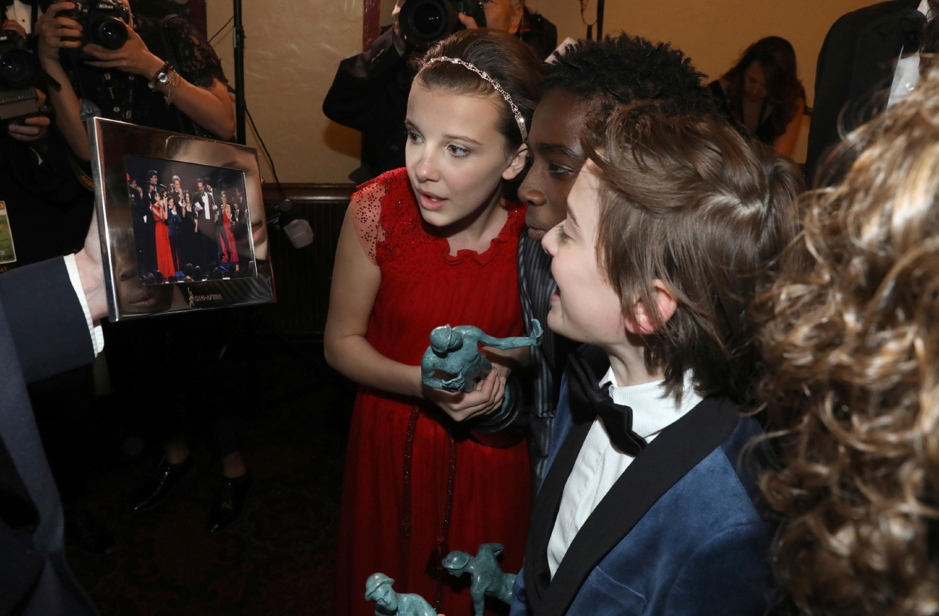 "Millie Bobby Brown, from left, Caleb McLaughlin, and Noah Schnapp appear backstage with their awards for outstanding performance by an ensemble in a drama series for ""Stranger Things"" at the 23rd annual Screen Actors Guild Awards at the Shrine Auditorium & Expo Hall on Sunday, Jan. 29, 2017, in Los Angeles. (Photo by Matt Sayles/Invision/AP)"