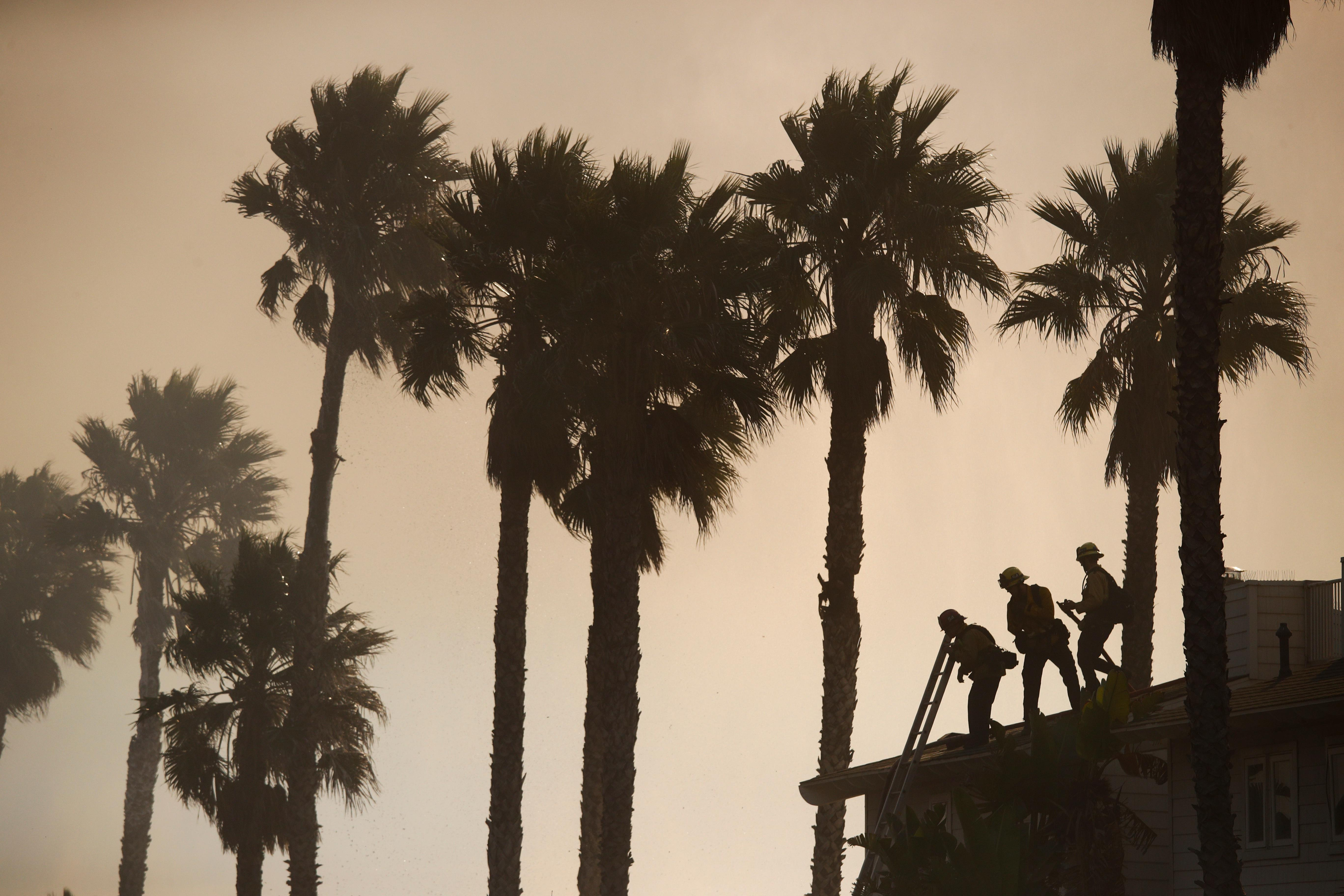 Three firefighters stand on the rooftop of a beach house to water down the property while battling a wildfire at Faria State Beach in Ventura, Calif., Thursday, Dec. 7, 2017. The wind-swept blazes have forced tens of thousands of evacuations and destroyed dozens of homes. (AP Photo/Jae C. Hong)