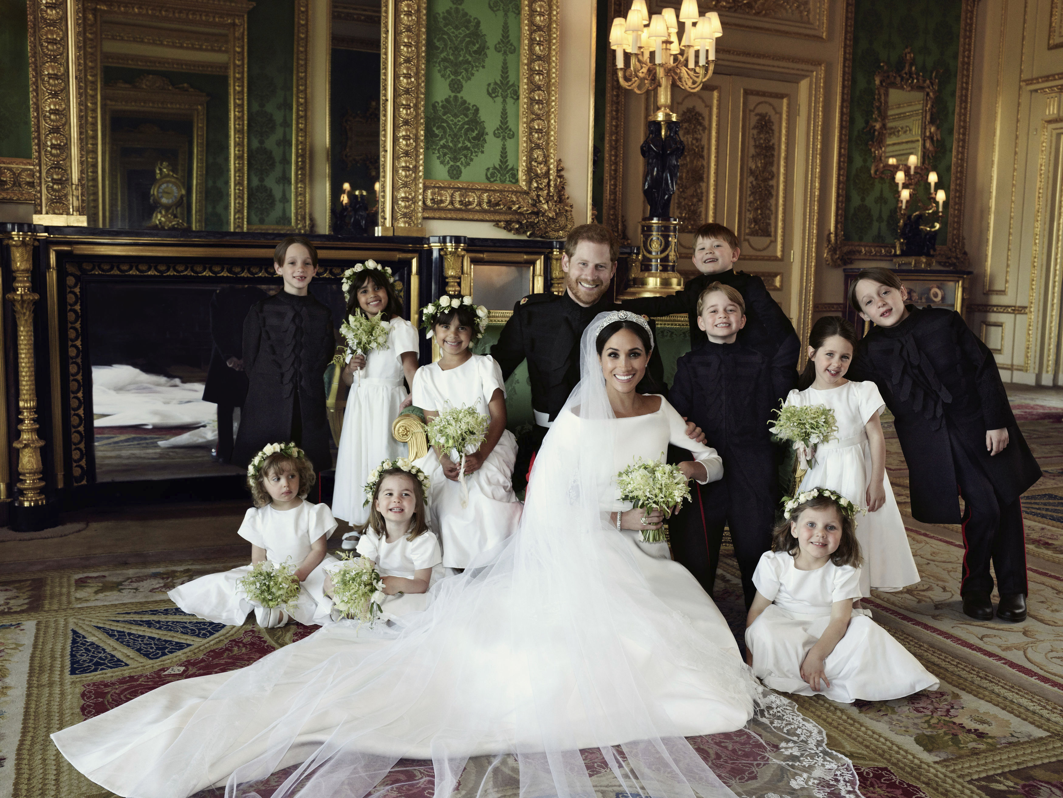 In this photo released by Kensington Palace on Monday May 21, 2018, shows an official wedding photo of Britain's Prince Harry and Meghan Markle, center, in Windsor Castle, Windsor, England, Saturday May 19, 2018. Others in photo from left, back row, Brian Mulroney, Remi Litt, Rylan Litt, Jasper Dyer, Prince George, Ivy Mulroney, John Mulroney; front row, Zalie Warren, Princess Charlotte, Florence van Cutsem. (Alexi Lubomirski/Kensington Palace via AP)