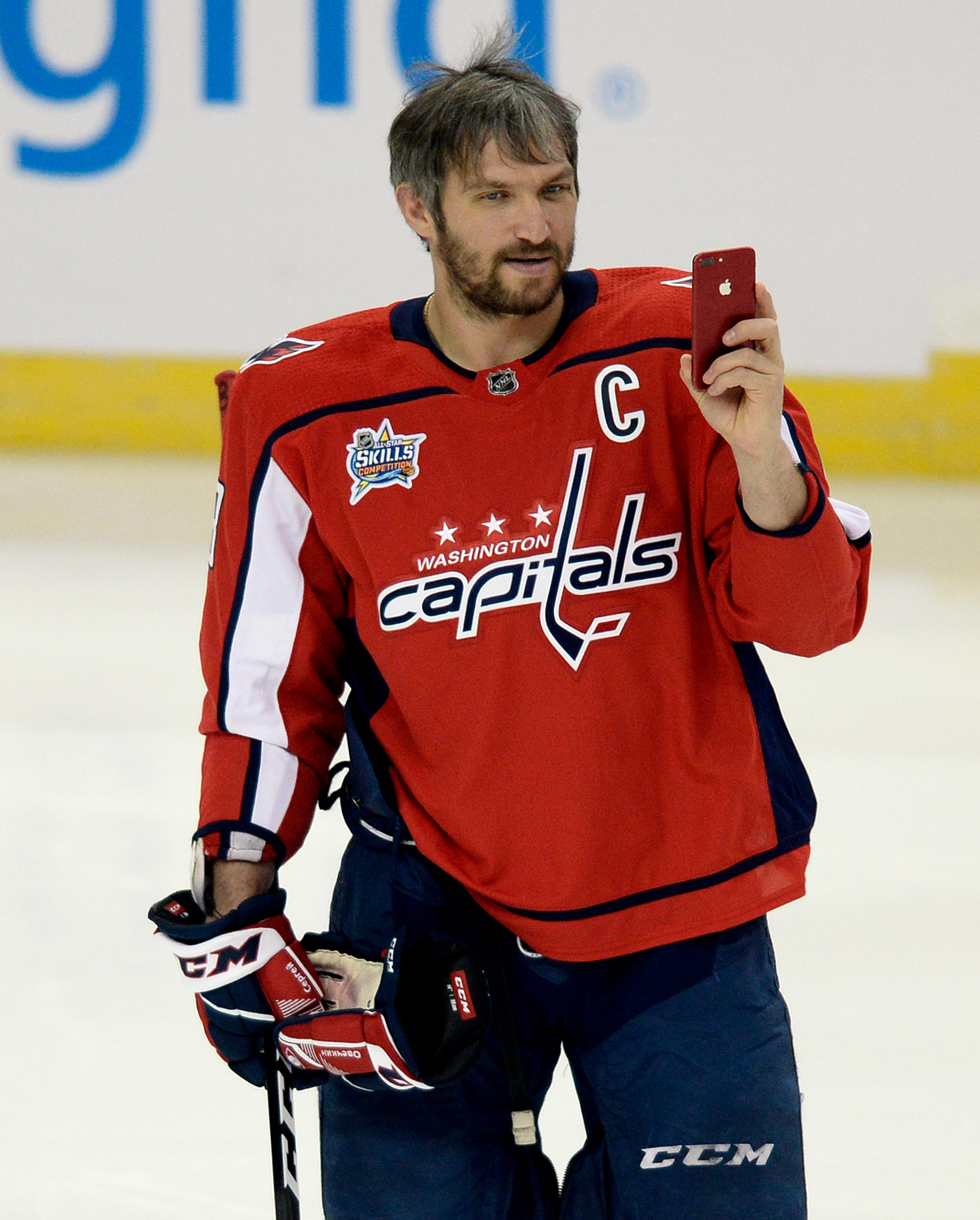Washington Capitals forward Alexander Ovechkin records on a smart phone before the Skills Competition, part of the NHL All-Star weekend events, Saturday, Jan. 27, 2018, in Tampa, Fla. (AP Photo/Jason Behnken)