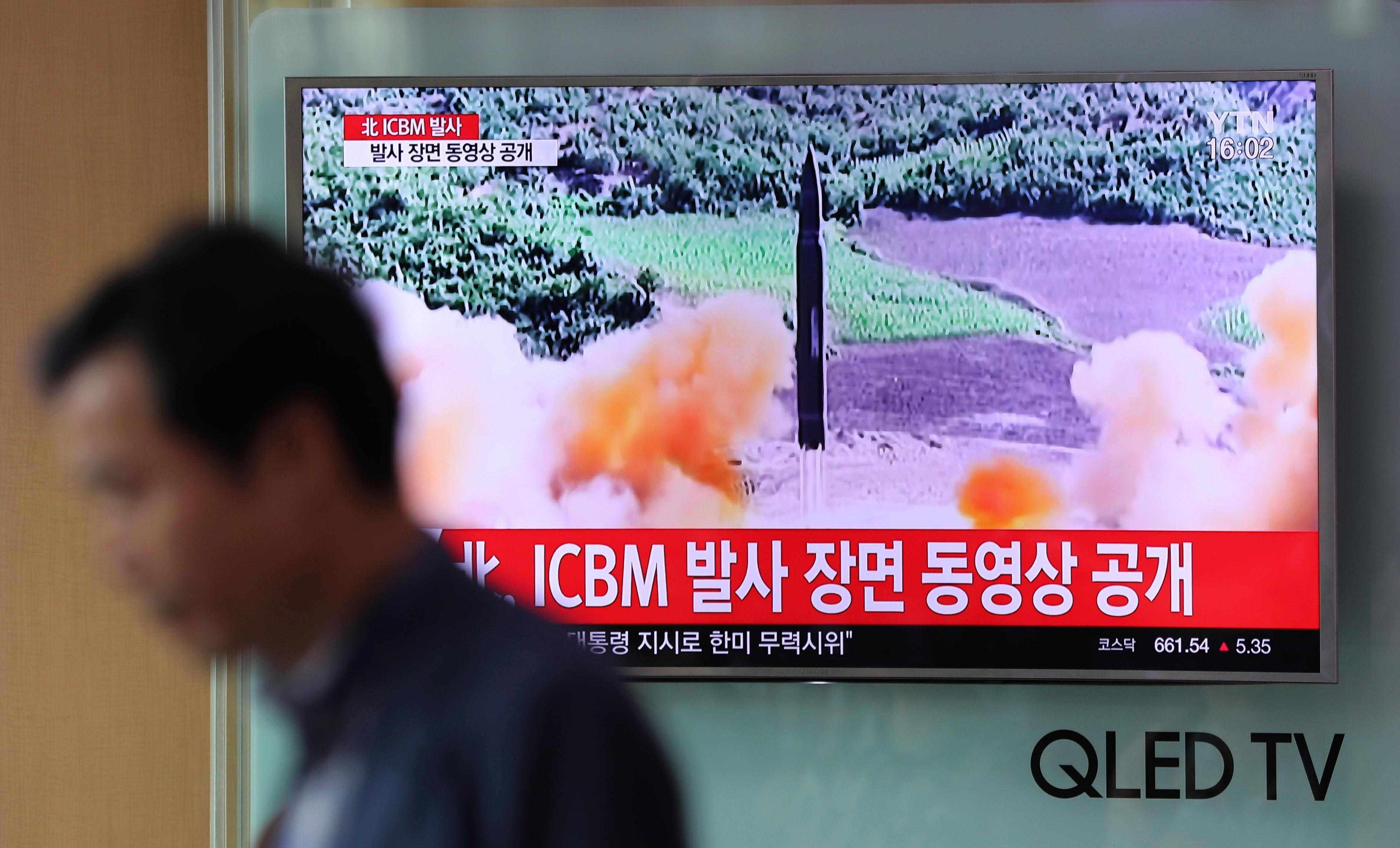 A man walks by a TV screen showing a local news program reporting about North Korea's missile firing at Seoul Train Station in Seoul, South Korea, Wednesday, July 5, 2017.  (AP Photo/Lee Jin-man)
