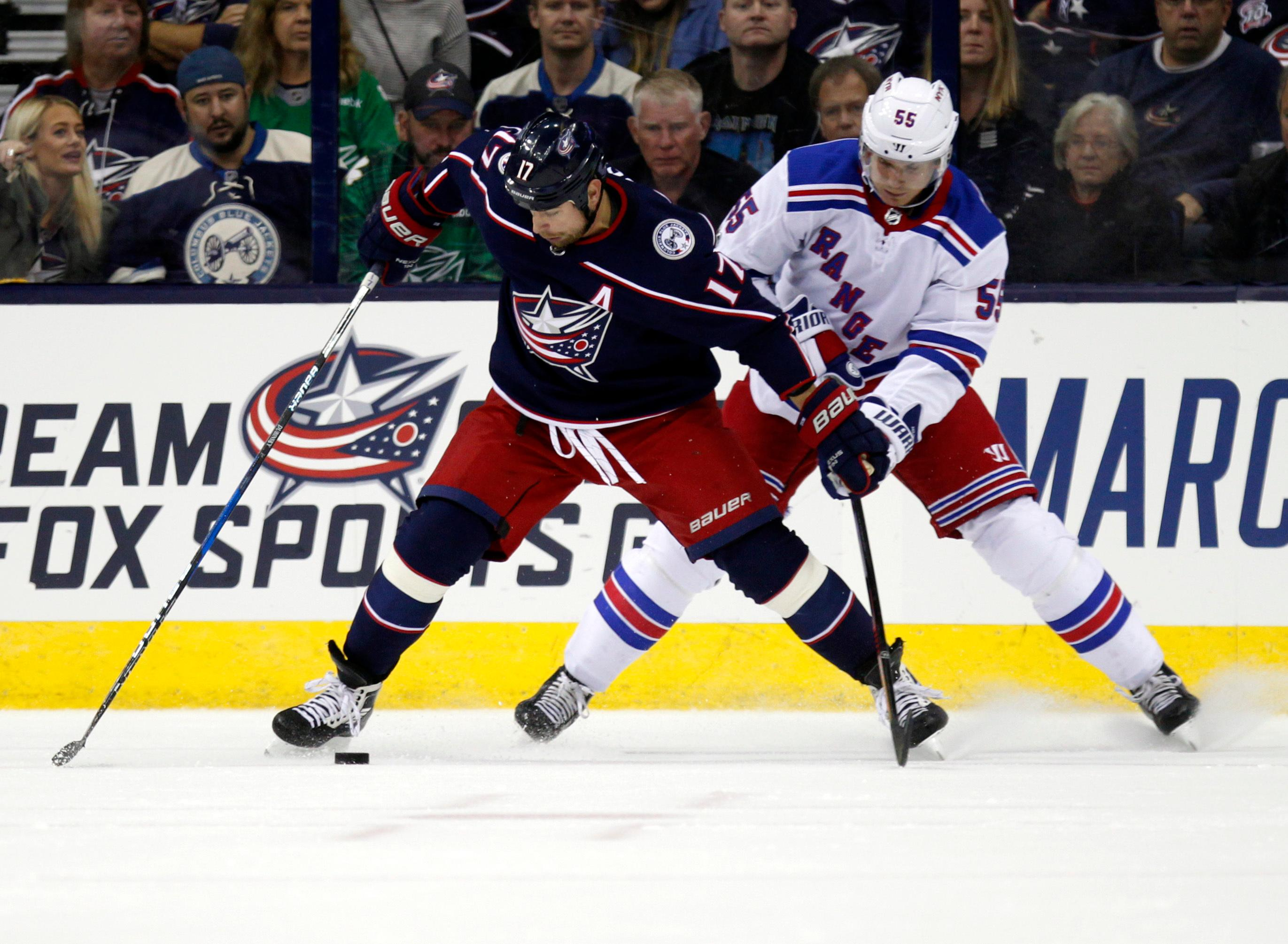 Columbus Blue Jackets forward Brandon Dubinsky, left, works against New York Rangers defenseman Nick Holden during the first period of an NHL hockey game in Columbus, Ohio, Friday, Oct. 13, 2017. (AP Photo/Paul Vernon)
