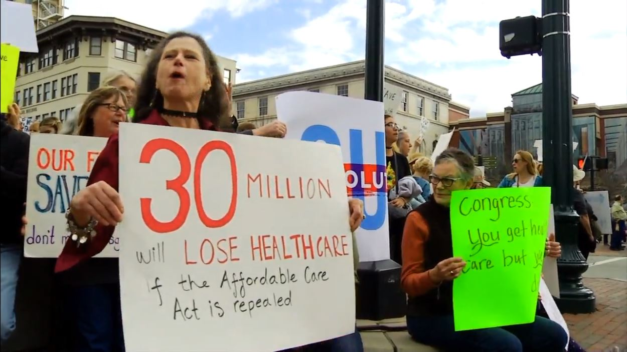 Hundreds marched through downtown Asheville on Sunday, part of an effort to help save the Affordable Care Act. (Photo credit: WLOS staff)