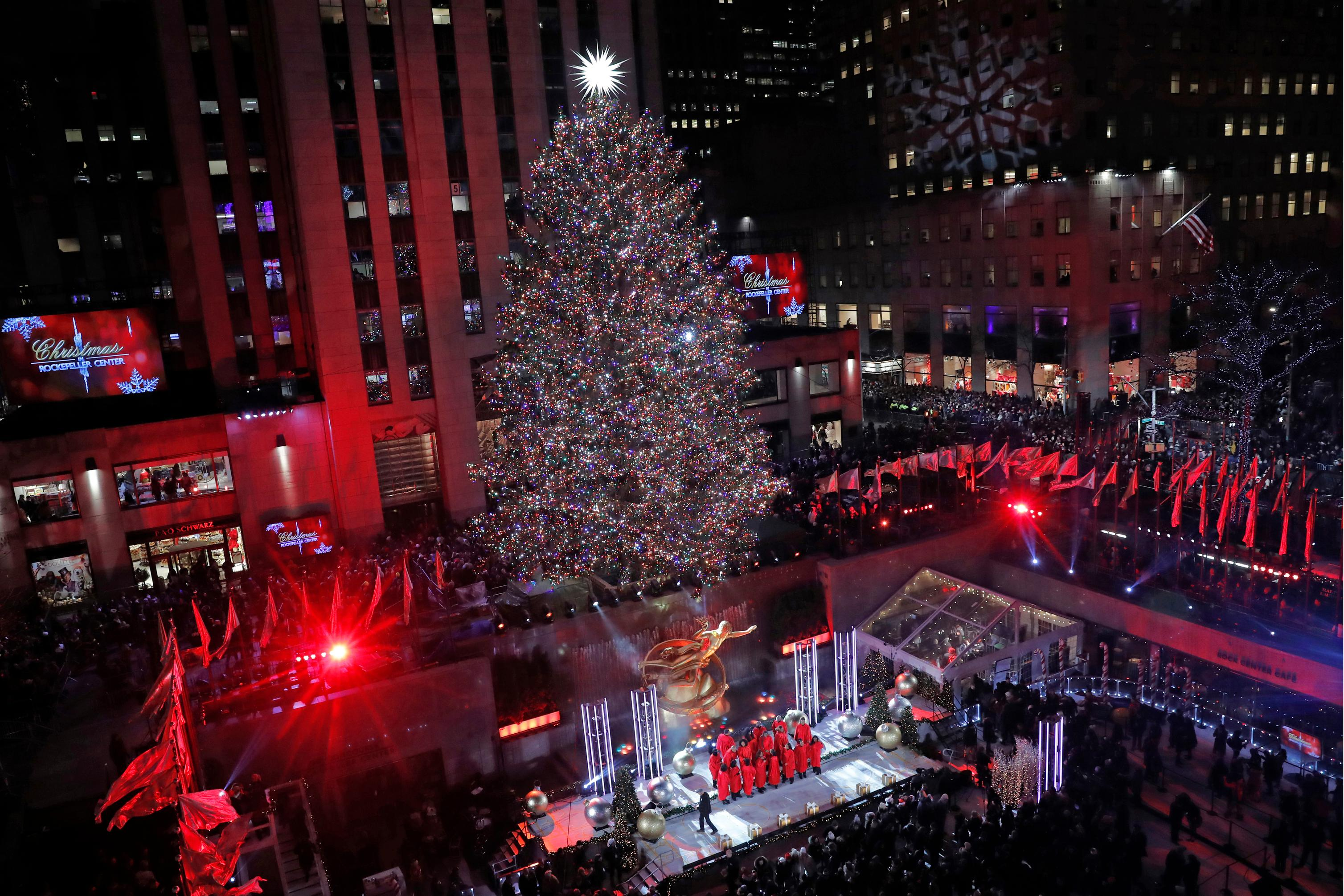 Singers gather on a stage beneath the Rockefeller Center Christmas Tree after the 77-foot high tree was illuminated in the 87th annual tree lighting ceremony, Wednesday, Dec. 4, 2019, in New York. (AP Photo/Kathy Willens)