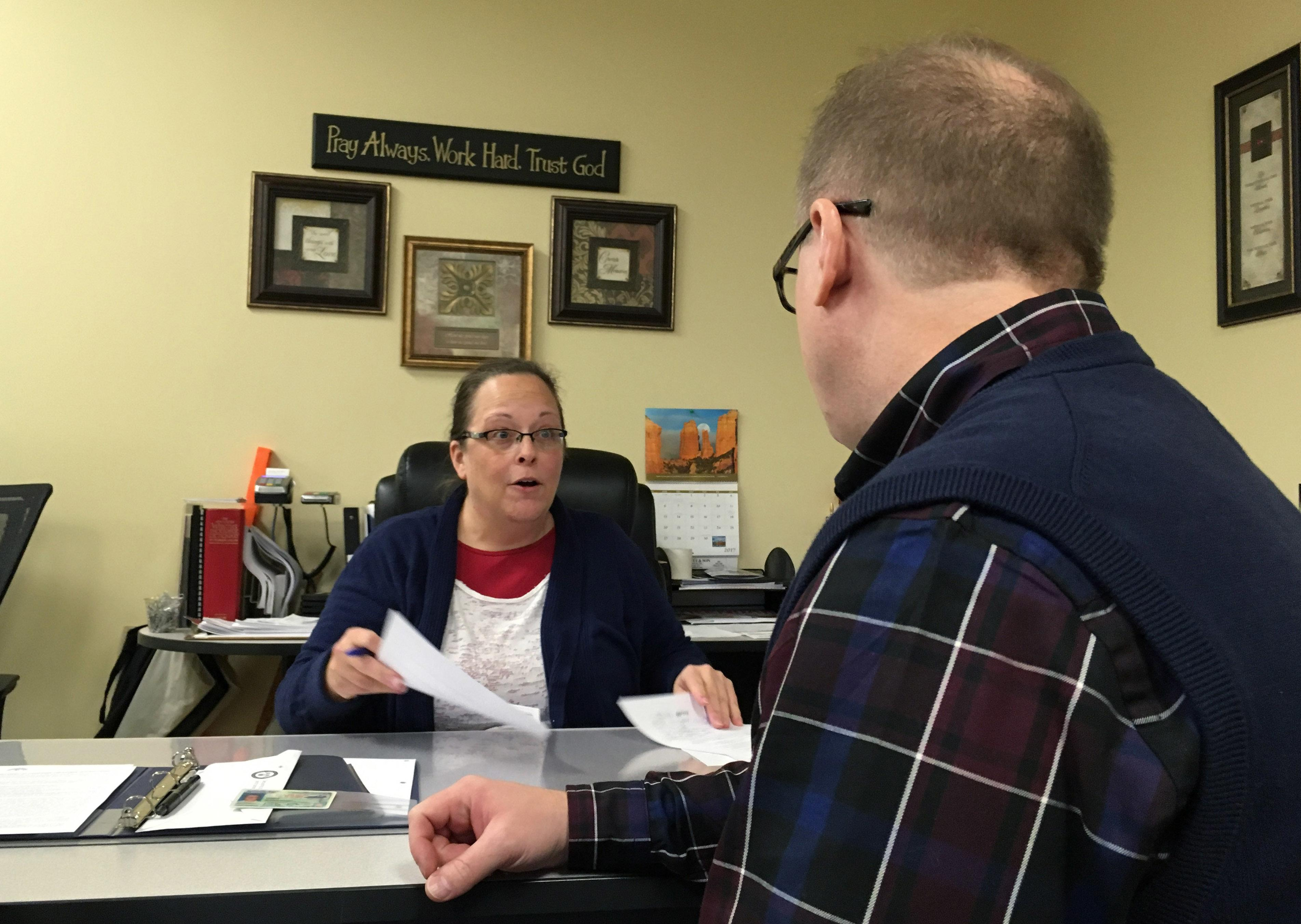 David Ermold, right, speaks with Clerk Kim Davis as he files to run for Rowan County Clerk Wednesday, Dec. 6, 2017,  in Morehead, Ky. Davis denied Ermold and his husband a marriage license two years ago because she was opposed to gay marriage for religious reasons. (AP Photo/Adam Beam)