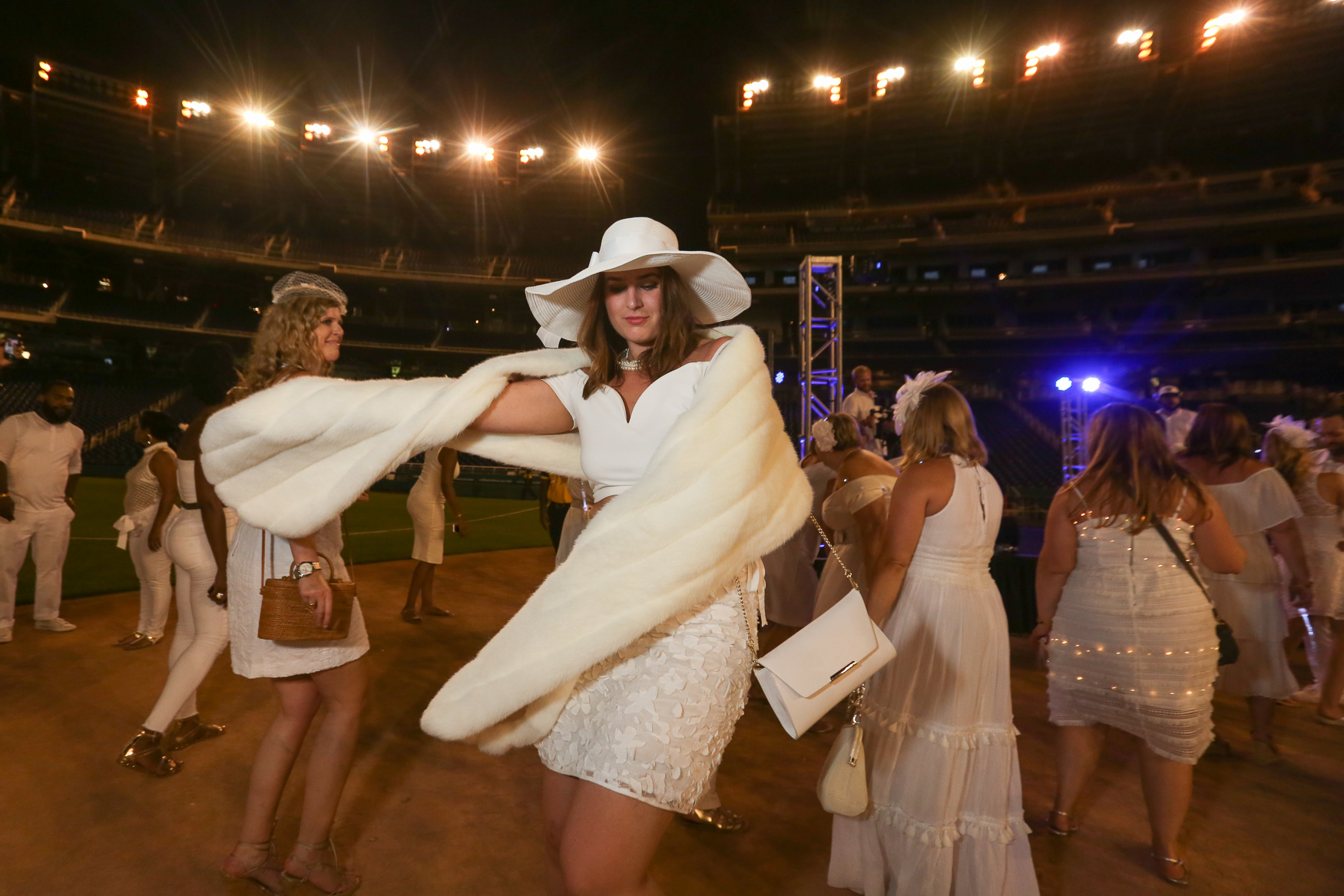 On August 25, 5,000 people donned their fanciest white garb and carried their tables, decorations and food to Nats Park for Dîner en Blanc, a spectacular pop-up picnic. Although attendees only learn of the location about an hour before the dinner starts, they go all out with spectacular tablescapes and delicious food. The event typically includes a napkin spinning ceremony and sparklers, although this year, attendees used electronic sparklers to preserve Nats Park. The evening concluded with dancing on the baseball diamond. (Amanda Andrade-Rhoades/DC Refined)
