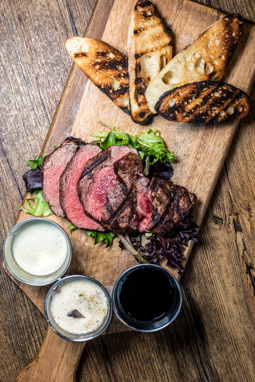 Sliced filet mignon: filet mignon thinly sliced and paired with red wine sauce, bleu cheese butter, and mushroom garlic sauce / Image: Catherine Viox{ }// Published: 3.7.20