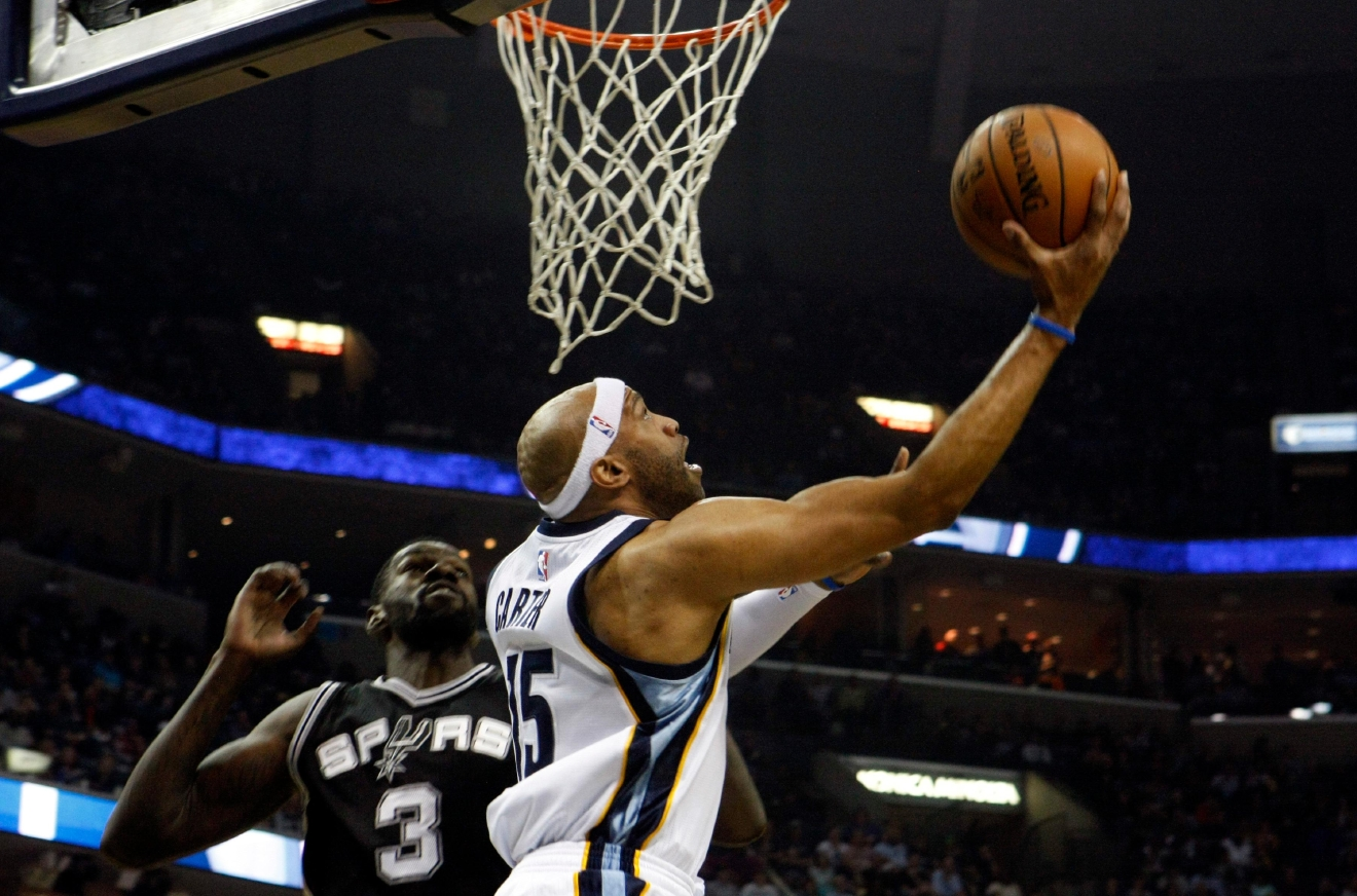 Memphis Grizzlies' Vince Carter, (15) shoots while being defended by San Antonio Spurs' Dewayne Dedmon (3) in the first half of an NBA basketball game Saturday, March 18, 2017, in Memphis, Tenn. (AP Photo/Karen Pulfer Focht)