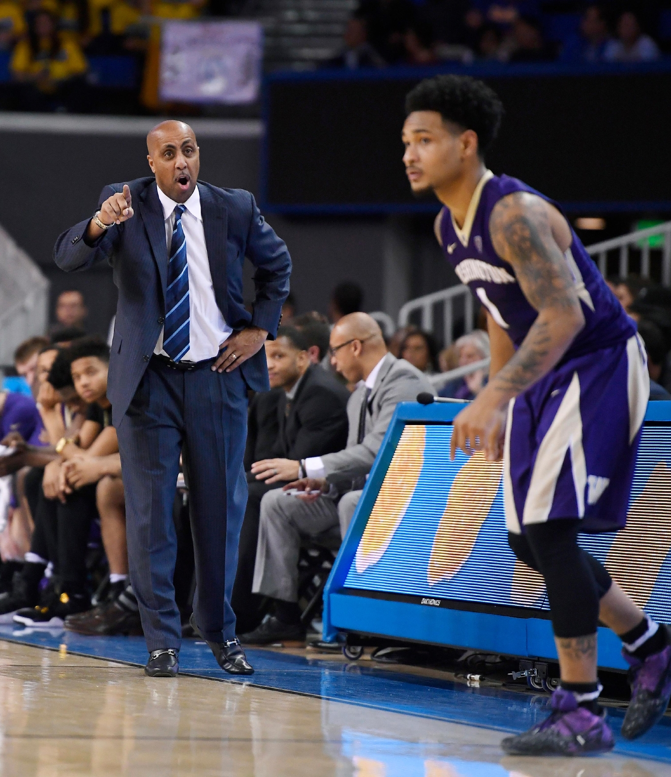 Washington coach Lorenzo Romar, left, yells instructions to guard David Crisp during the second half of the team's NCAA college basketball game against UCLA, Wednesday, March 1, 2017, in Los Angeles. UCLA won 98-66. (AP Photo/Mark J. Terrill)