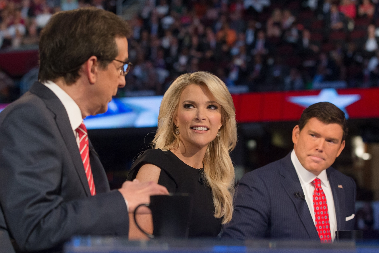 FILE - In this Aug. 6, 2015 file photo, FOX News moderators Megyn Kelly, center, and Bret Baier, right, listens as Chris Wallace, left, beings introductions during the first Republican presidential debate in Cleveland. Anticipating another appearance on a debate stage with Donald Trump, Kelly says their public feud hasn't affected her preparation and she doesn't expect a renewal of hostilities with the Republican presidential front runner. She is moderating a debate with colleagues Bret Baier and Chris Wallace, Thursday, March 3, at Detroit's Fox Theater from 9 to 11 p.m. ET. (AP Photo/John Minchillo, File)