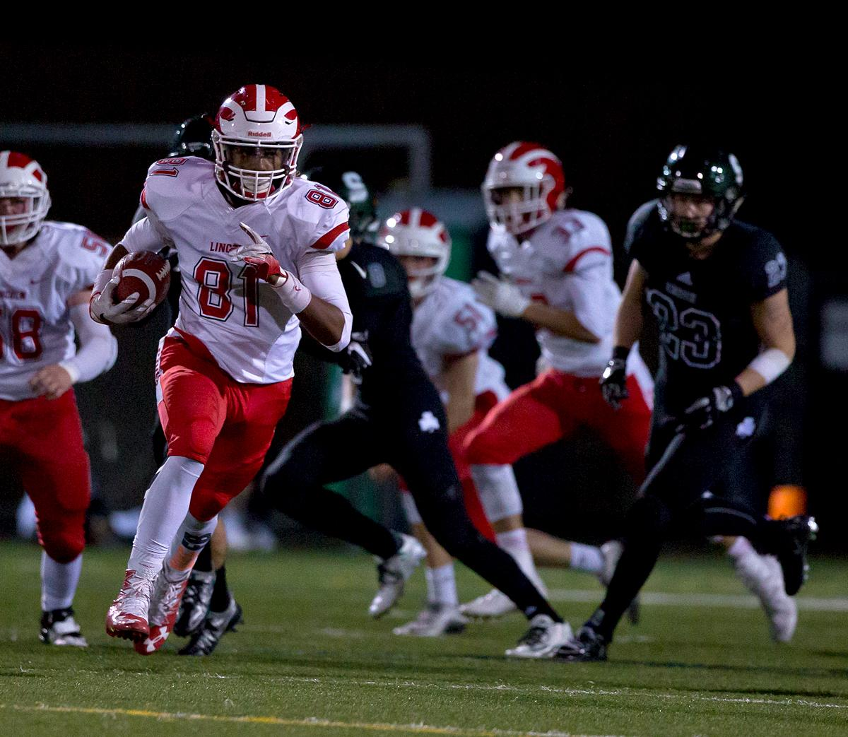 Lincoln wide receiver Phil Rodgers (#81) sprints away from the Sheldon offense after catching a pass. The Sheldon Irish defeated the Lincoln Cardinals 38 to 28 to advance to the quarterfinals of the OSAA 6A playoffs. Photo by Ben Lonergan, Oregon News Lab