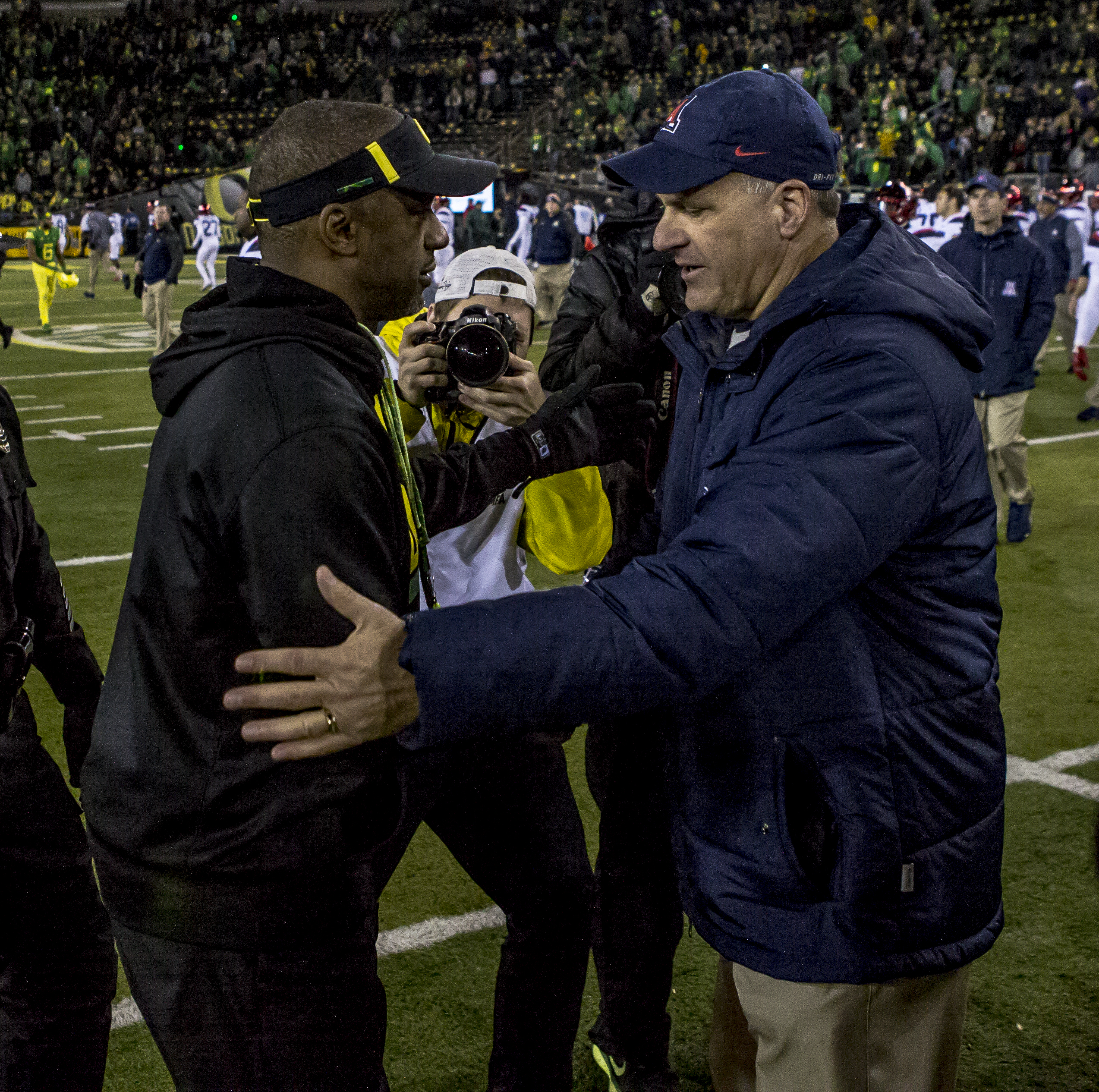 Oregon Head Coach Willie Taggart greets Arizona Head Coach Rich Rodriguez following the game. The Oregon Ducks defeated the Arizona Wildcats 48 to 28 during a chilly evening game at Autzen Stadium on November 18, 2017. Photo by Ben Lonergan, Oregon News Lab