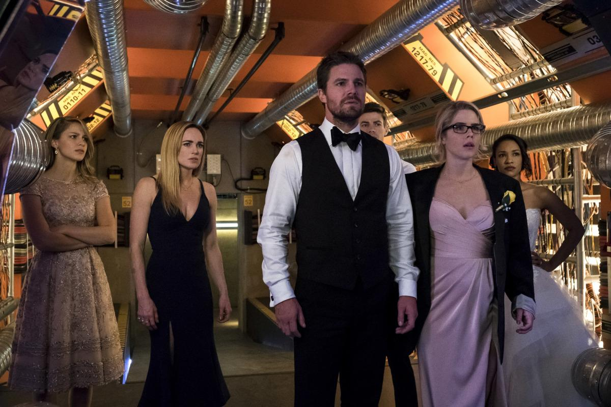 "Arrow -- ""Crisis on Earth-X, Part 2"" -- AR608c_0113b.jpg -- Pictured (L-R): Melissa Benoist as Kara, Caity Lotz as Sara Lance, Stephen Amell as Oliver Queen, Grant Gustin as Barry Allen, Emily Bett Rickards as Felicity Smoak, and Candice Patton as Iris West -- Photo: Katie Yu/The CW -- �© 2017 The CW Network, LLC. All Rights Reserved"