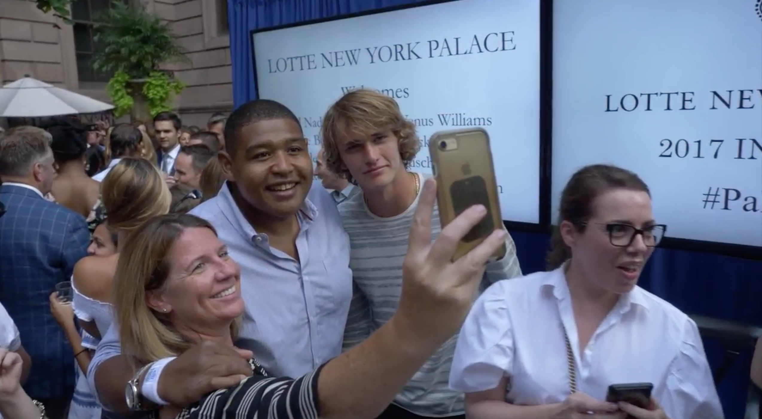 Omar Miller and Alexander Zverev take a selfie with fans at a badminton tournament