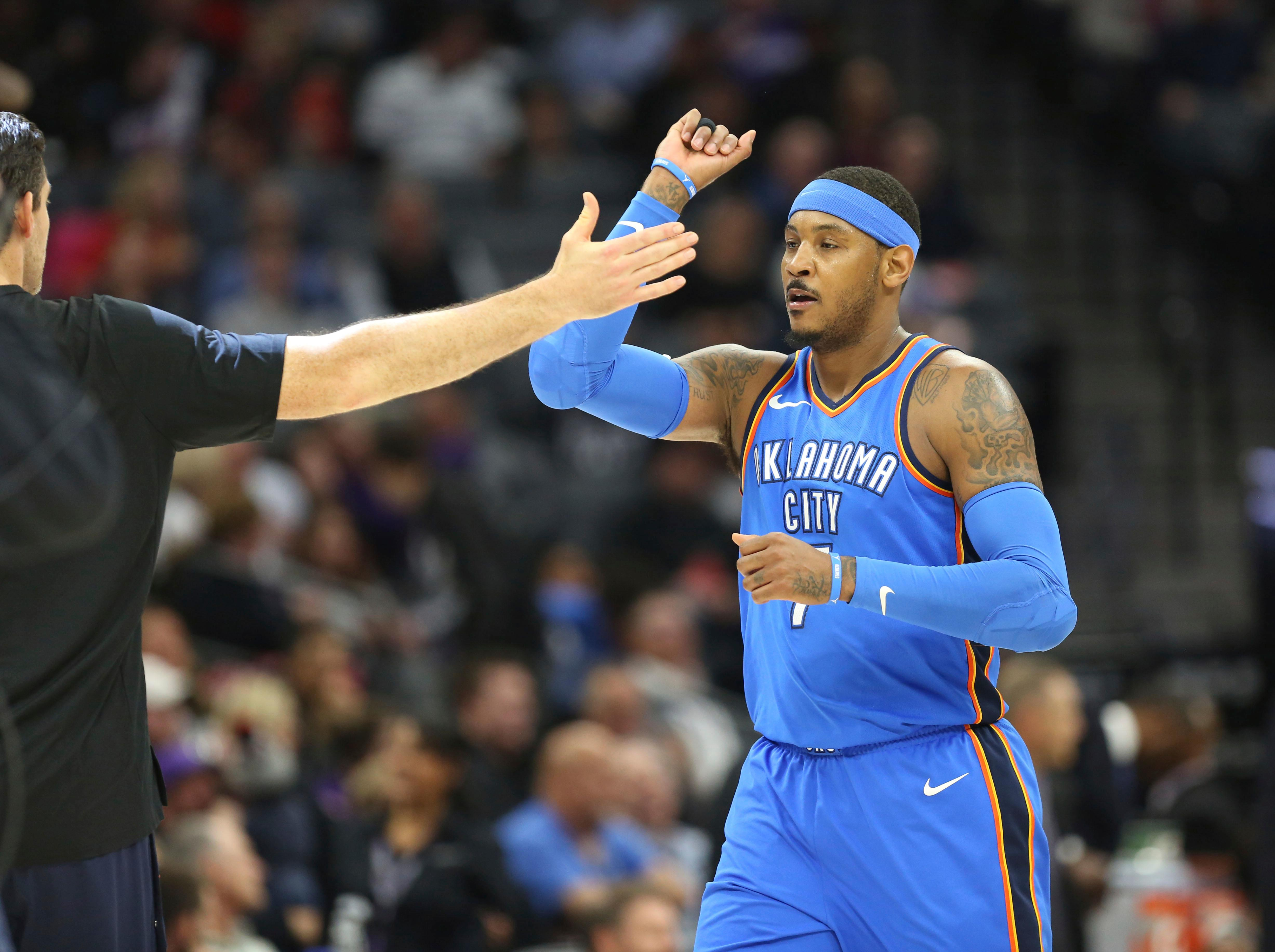 Oklahoma City Thunder forward Carmelo Anthony (7) is greeted by teammates at the end of the first half of an NBA basketball game against the Sacramento Kings in Sacramento, Calif., Thursday, Feb. 22, 2018. (AP Photo/Steve Yeater)