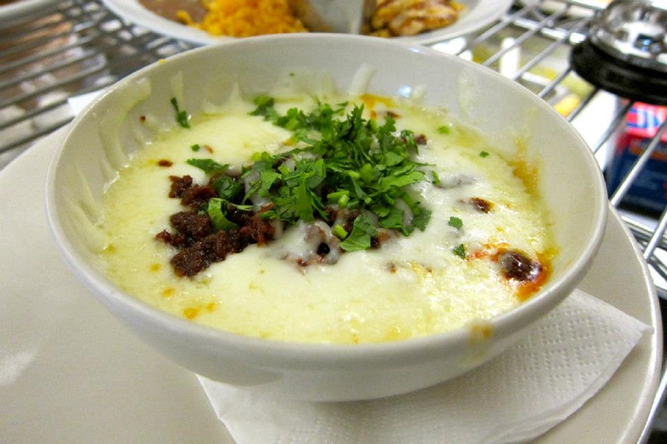 This is a baked queso Oaxaca topped with chorizo and cilantro or chapped carne asada, then topped with strips of poblano pepper and corn. It's served with handmade tortillas and salsa roja. (Photo Courtesy:{&amp;nbsp;}Fogón Cocina Mexicana)<p></p>