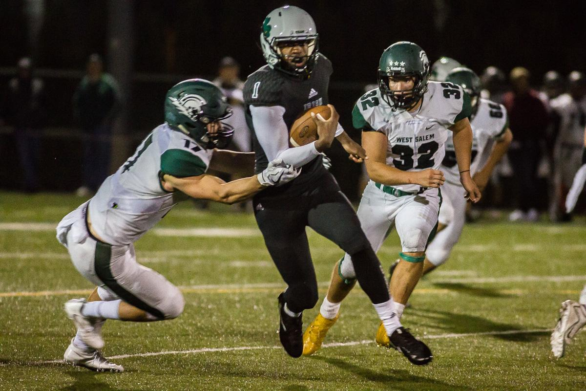 Sheldon quarterback Michael Johnson (#1) evades the West Salem defenders on his way to a touch down. On a rainy Monday evening Sheldon defeated West Salem 41-7 at home. The game had been postponed from Friday due to unhealthy levels of smoke in the atmosphere due to nearby forest fires. Photo by Dillon Vibes