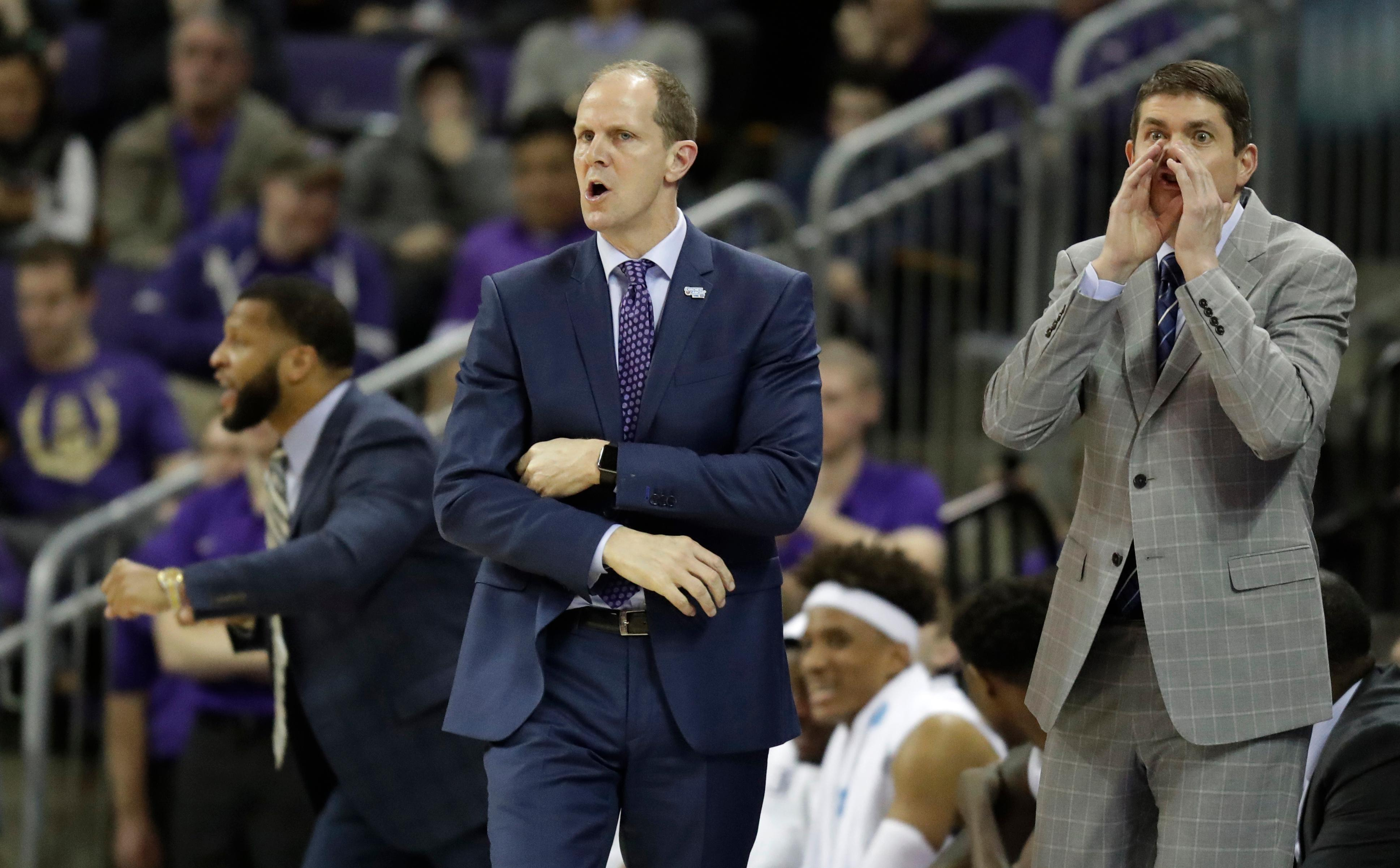 In this Sunday, Jan. 28, 2018 photo, Washington head coach Mike Hopkins, center, calls to his team along with assistants Will Conroy, left, and Dave Rice, right,, during the first half of an NCAA college basketball game against Washington State in Seattle. One of the most surprising stories in college basketball is what Hopkins is doing in his first season at Washington and how the Huskies are in the conversation for an NCAA bid entering February. (AP Photo/Ted S. Warren)