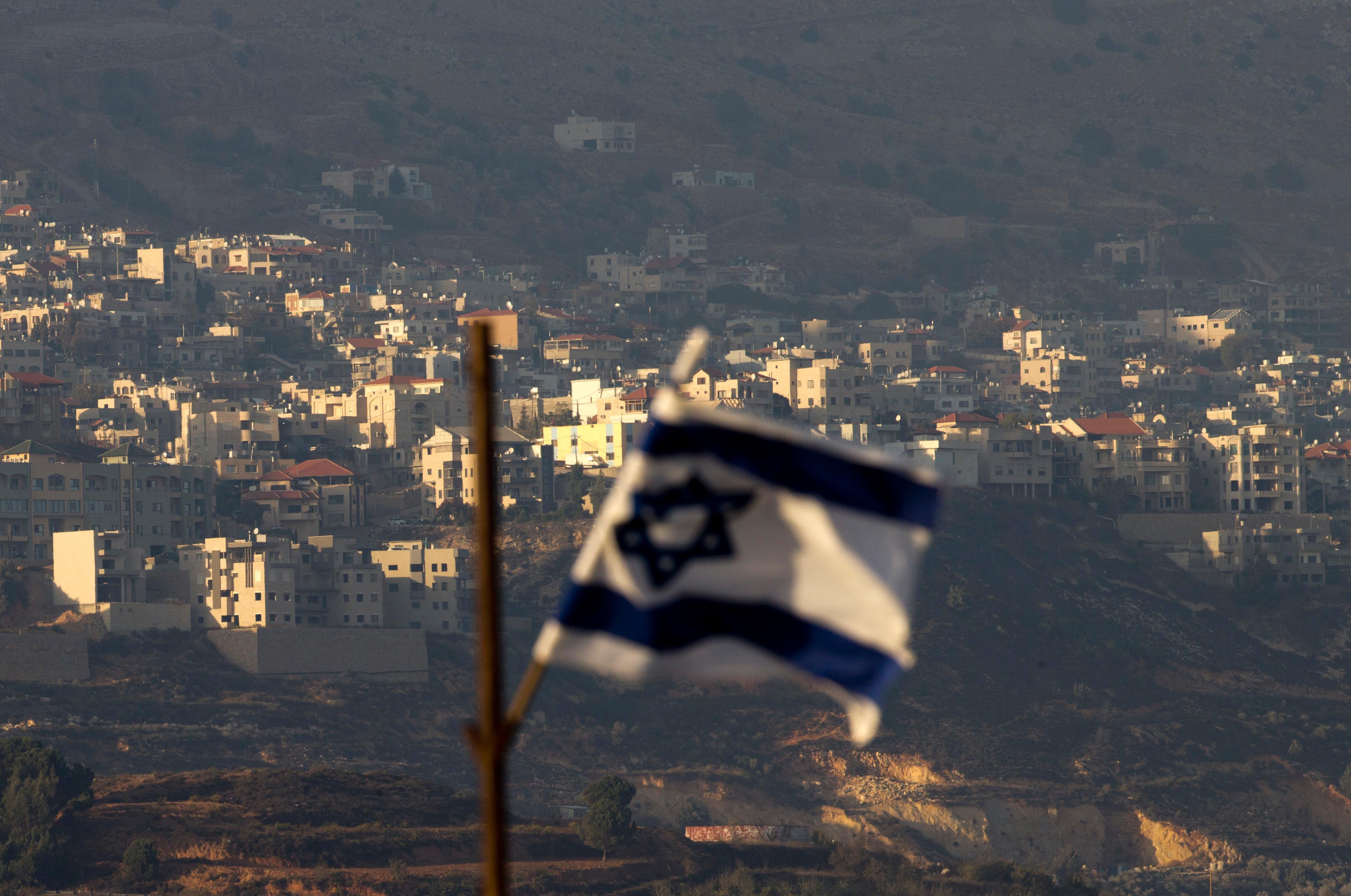 FILE - In this file photo dated Thursday, Oct. 11, 2018, an Israeli flag in front of the village of Majdal Shams in the Israeli-controlled Golan Heights.(AP Photo/Ariel Schalit, FILE)