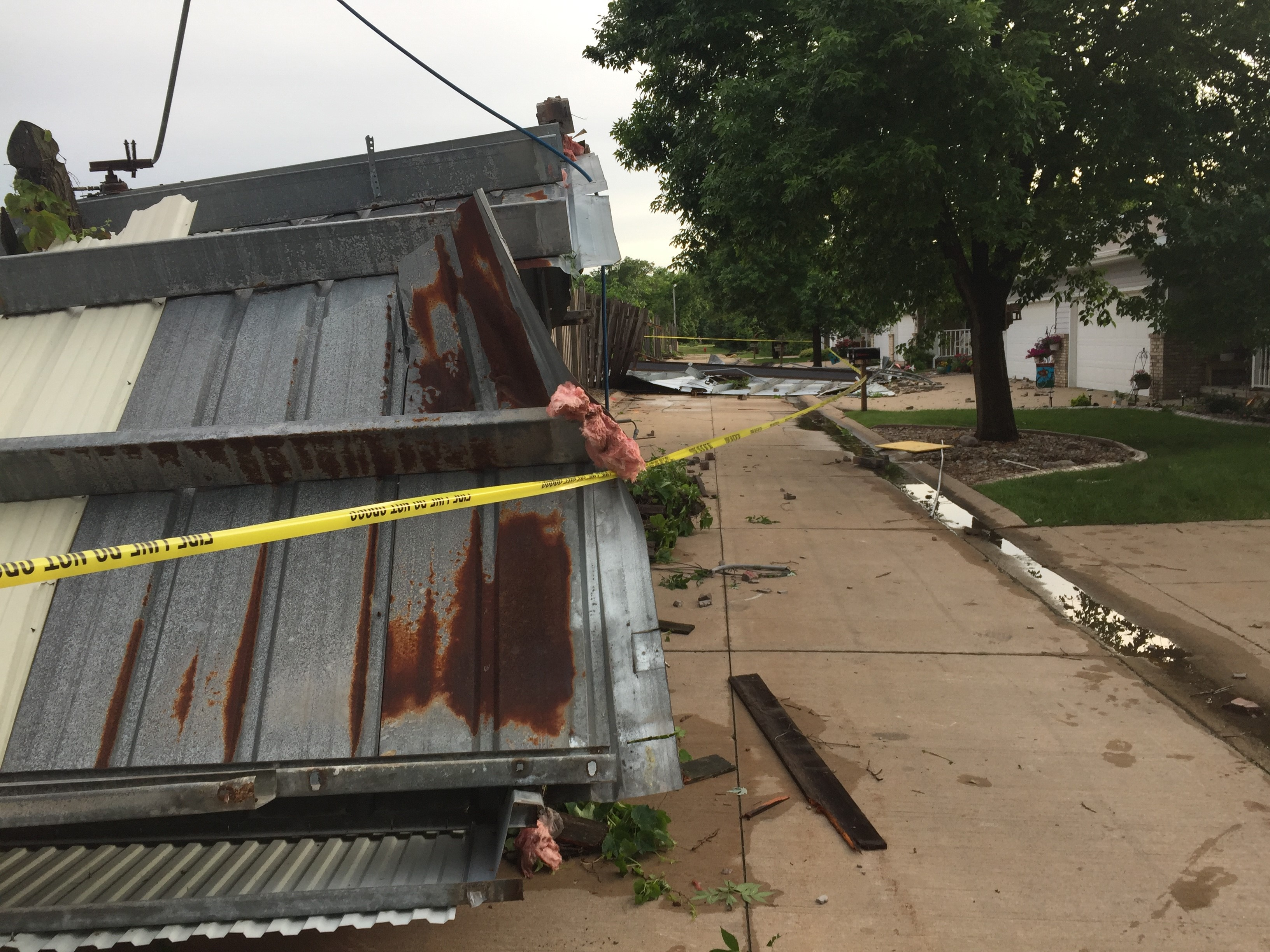 The roof of the Best Wash in Kimberly is resting on a nearby home after storms moved through, June 14, 2017. (WLUK/Chris Bourassa)