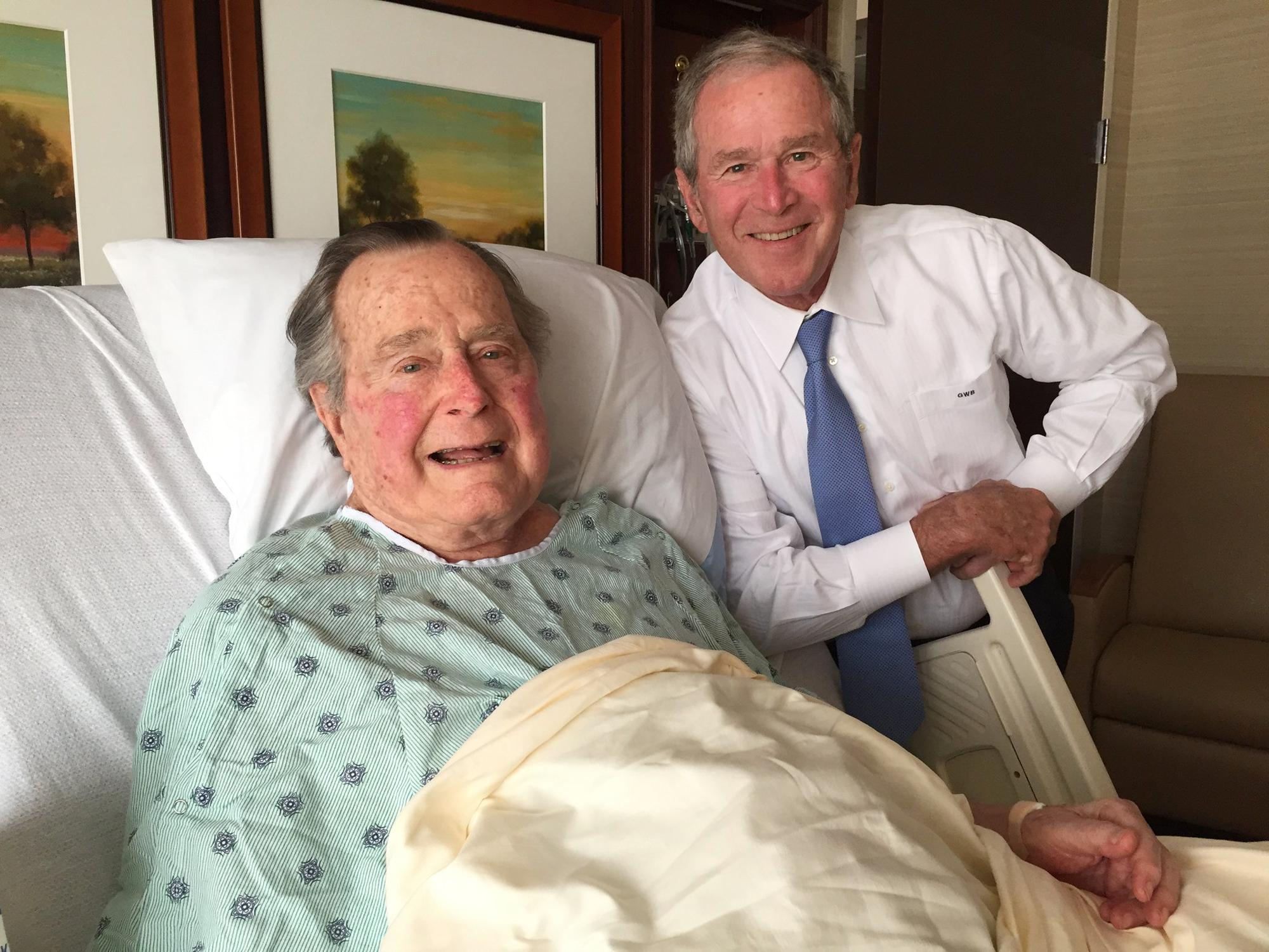 FILE - This April 20, 2017, file photo provided by the Office of George H.W. Bush shows former President George H.W. Bush, left, posing with his son former President George W. Bush at Houston Methodist Hospital in Houston where he was recovering from a mild case of pneumonia after being admitted on April 14. Bush spokesman Jim McGrath said in a statement Bush was discharged from the hospital on Friday, April 28, 2017. After the pneumonia was treated, Bush remained hospitalized due to chronic bronchitis. (Evan Sisley/Office of George H.W. Bush via AP, File)