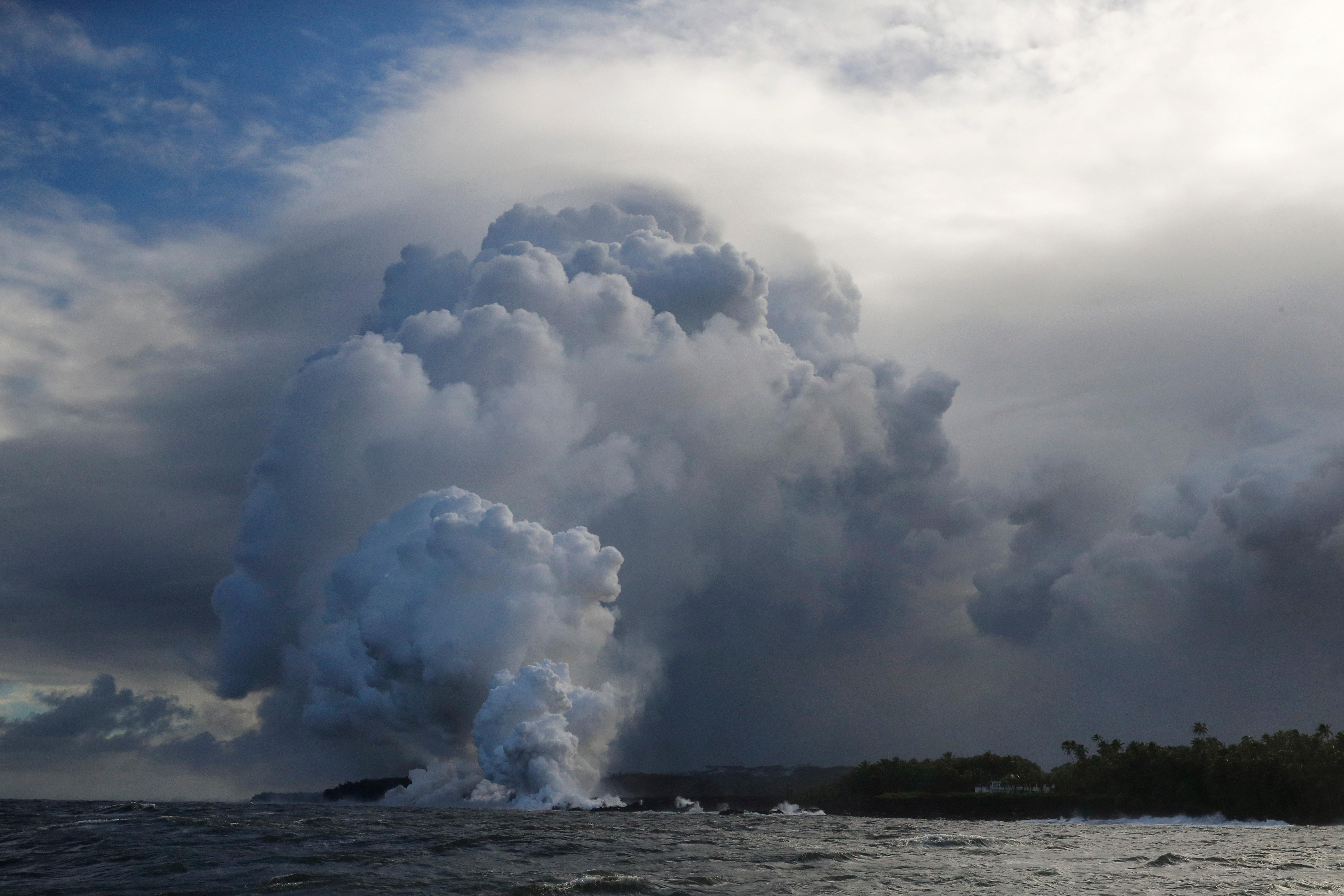 A plume of steam rises as lava enters the ocean near Pahoa, Hawaii, Sunday, May 20, 2018. Kilauea volcano that is oozing, spewing and exploding on Hawaii's Big Island has gotten more hazardous in recent days, with rivers of molten rock pouring into the ocean Sunday and flying lava causing the first major injury. (AP Photo/Jae C. Hong)