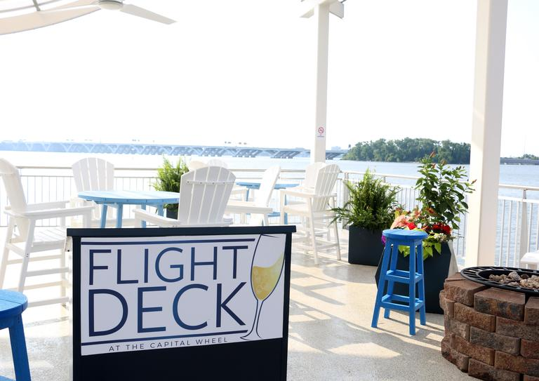 As of Memorial Day weekend, visitors to the National Harbor's Capital Wheel can now enjoy a few tipples as they ride the wheel. The new outdoor lounge, called Flight Deck, serves champagne, beer, wine and specialty cocktails, which guests can take on the Capital Wheel with them as they overlook the Potomac River. DC Refined hosted an intimate group of 35 readers for a sunset happy hour to celebrate the launch of Flight Deck. Guests enjoyed drinks, nibbles, rides on the wheel and a few giveaways. (Image: Jai Williams)