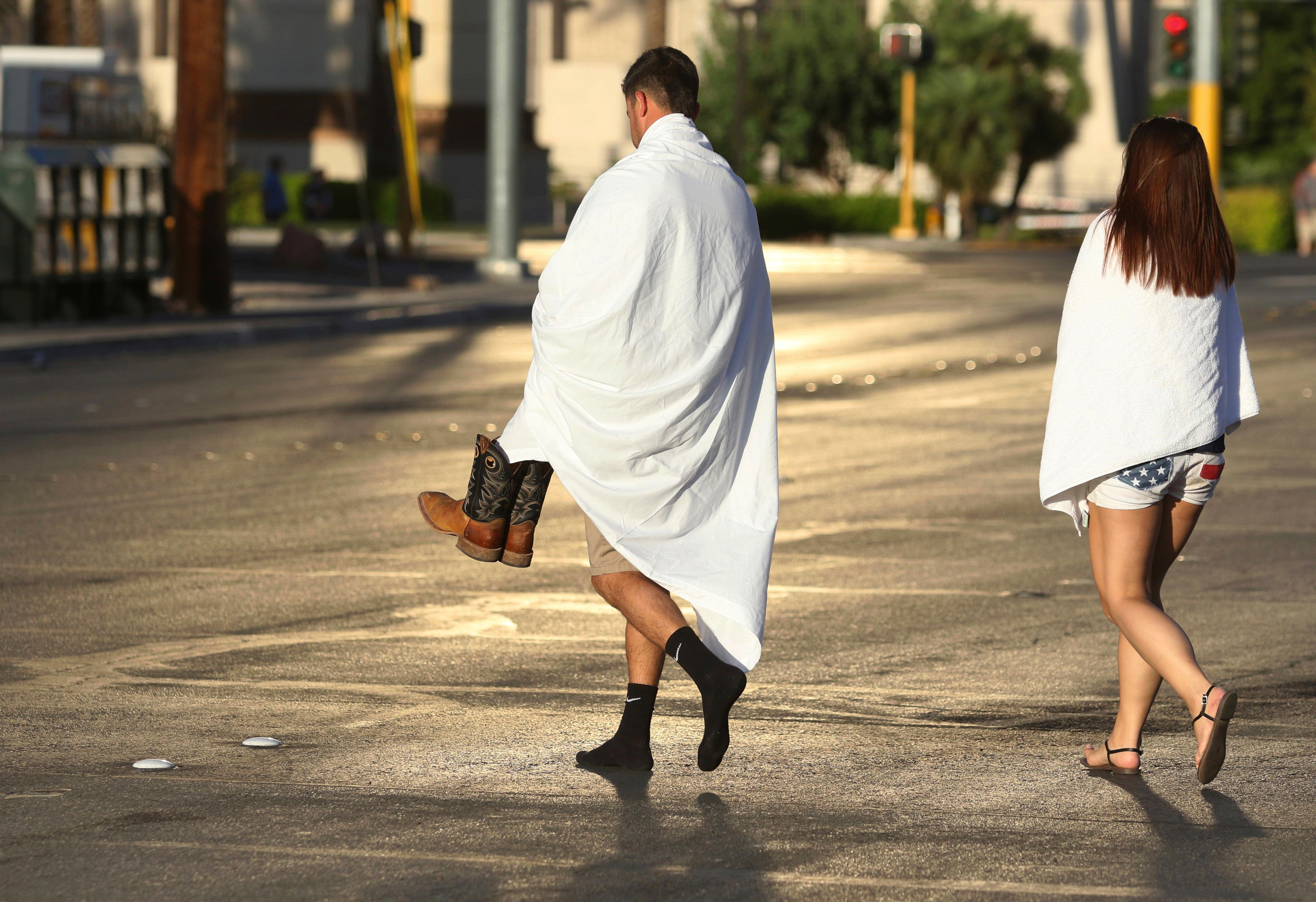 People walk near the Las Vegas Strip shortly after sunrise Monday, Oct. 2, 2017, in Las Vegas. A deadly shooting occurred Sunday at a music festival on the Las Vegas Strip. (AP Photo/Ronda Churchill)