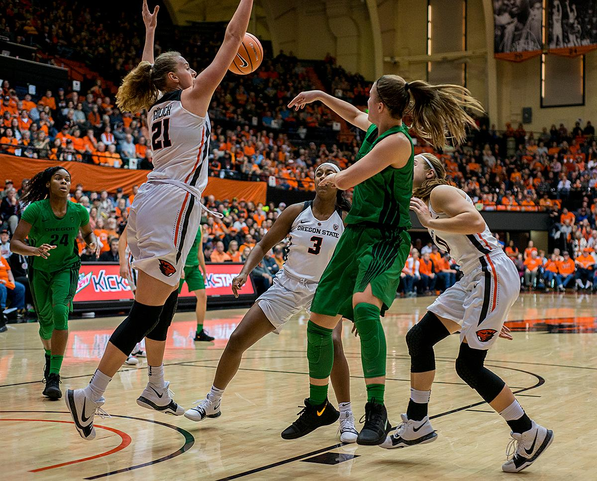 Oregon Ducks guard Sabrina Ionescu (#20) passes to teammate Ruthy Hebard (#24) as the Oregon State Beavers defense closes in.                  The Oregon Ducks were defeated by the Oregon State Beavers 85-79 on Friday night in Corvallis. Sabrina Ionescu scored 35 points and Ruthy Hebard added 24. The Ducks will face the Beavers this Sunday at 5 p.m. at Matthew Knight Arena. Photo by Abigail Winn, Oregon News Lab