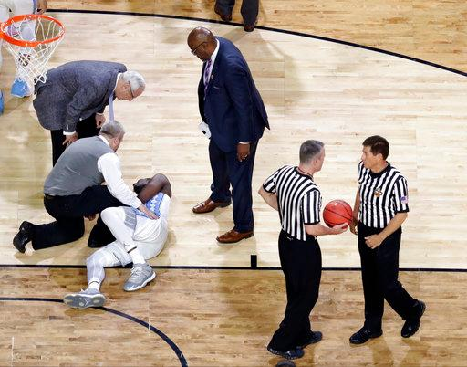 North Carolina head coach Roy Williams, left, checks on injured forward Theo Pinson during the first half against Oregon in the semifinals of the Final Four NCAA college basketball tournament, Saturday, April 1, 2017, in Glendale, Ariz. (AP Photo/David J. Phillip)