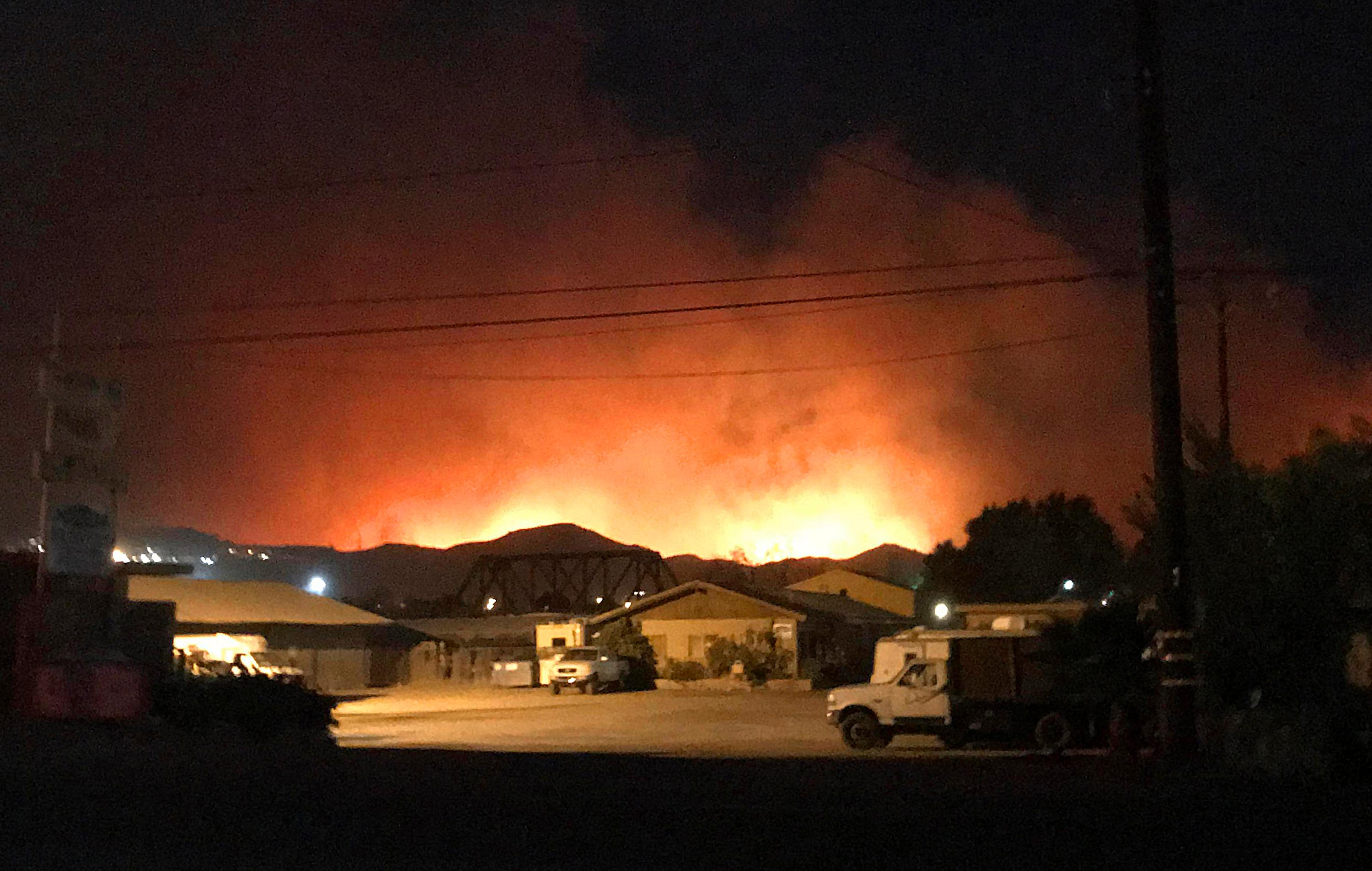 Flames from a wildfire loom up over a neighborhood in Santa Paula, Calf., Monday, Dec. 4, 2017. Ventura County fire officials say the blaze broke out Monday east of Santa Paula, a city of 30,000 people about 60 miles northwest of downtown Los Angeles. (Megan Diskin/The Ventura County Star via AP)<p></p>