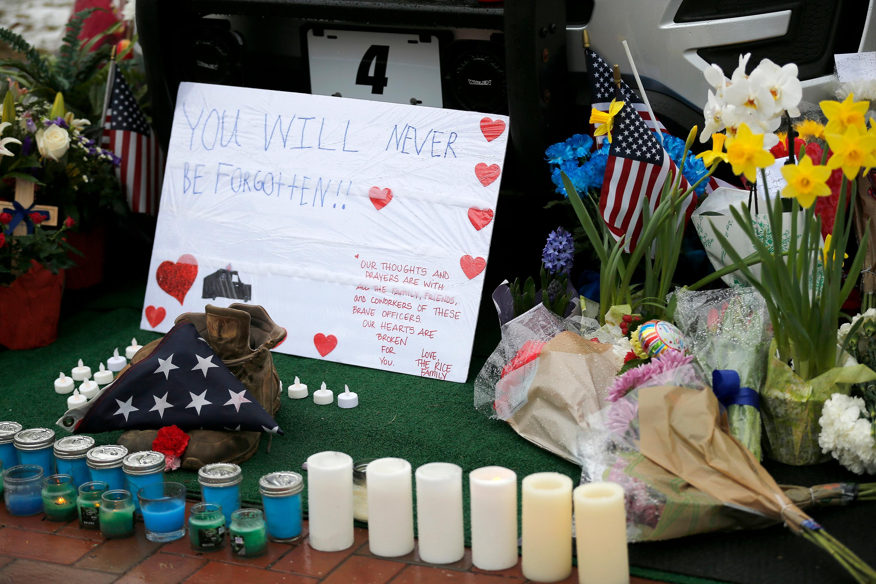 Mourners gather and leave flowers on a police cruiser parked in front of City Hall in Westerville, Ohio, on Sunday, Feb. 11, 2018. Westerville police officers Anthony Morelli and Eric Joering were killed in the line of duty Saturday when a suspect opened fire on them as they responded to a call at a residence.(Sam Greene/The Cincinnati Enquirer via AP)