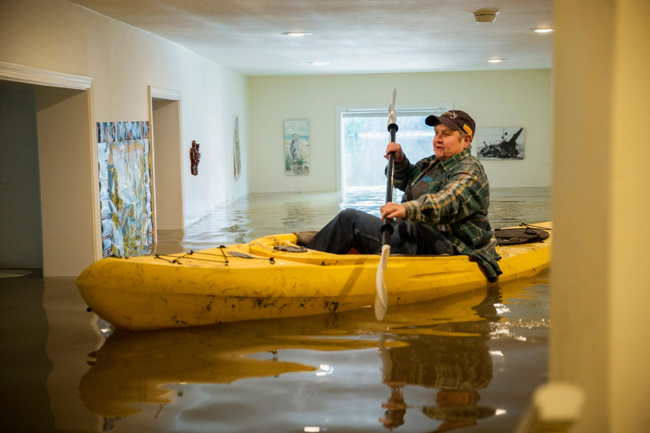 Lorin Doeleman uses a kayak to check her flooded home on Wednesday, Jan. 11, 2017, in Guerneville, Calif. She is moving her belongings to her Sacramento home. Forecasters said the brunt of a weather system had passed after delivering the heaviest rain in a decade to parts Northern California and Nevada. (Santiago Mejia/San Francisco Chronicle via AP)